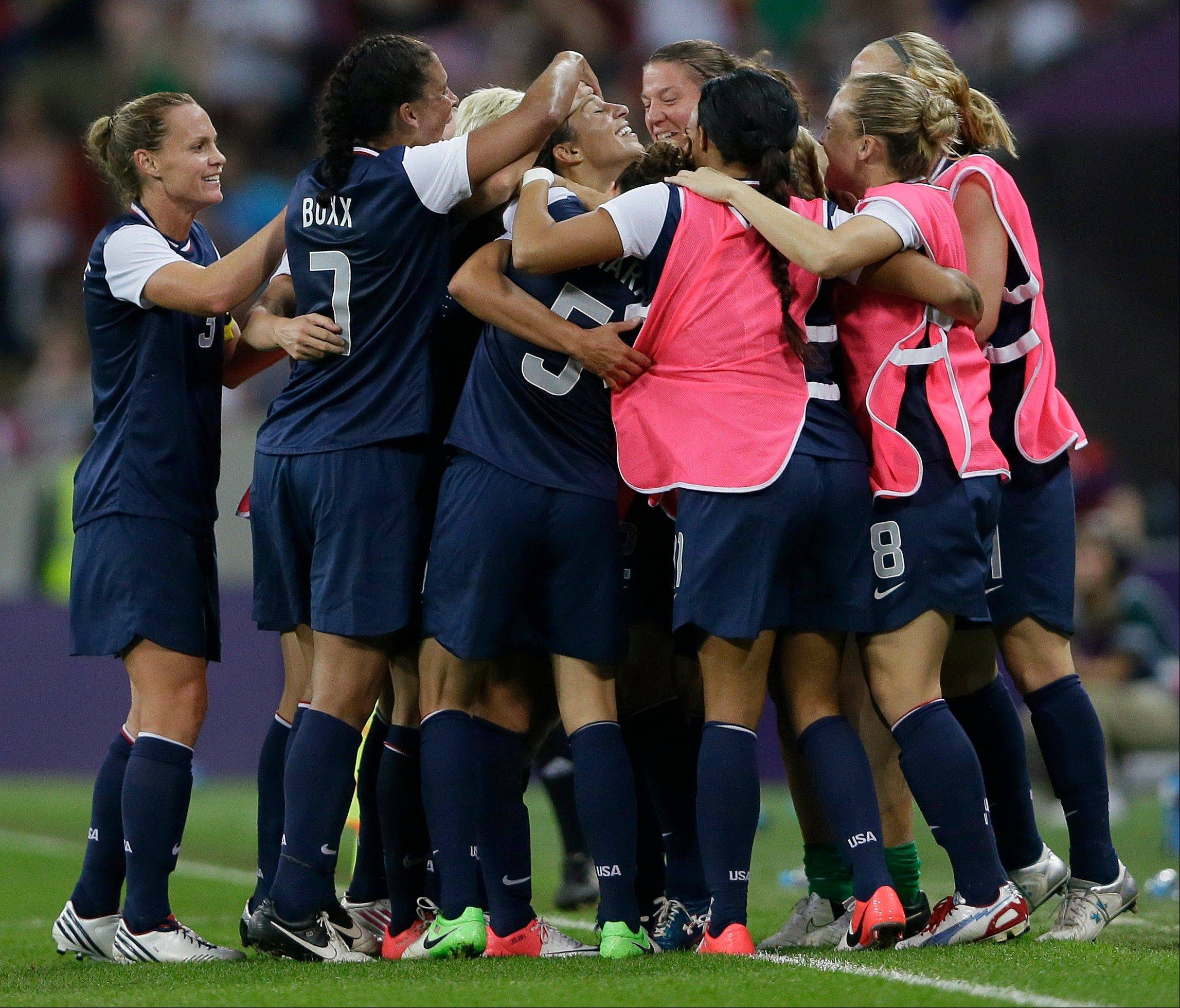 The United States' Carli Lloyd, center, celebrates Thursday with teammates after scoring her second goal during the gold medal match against Japan.