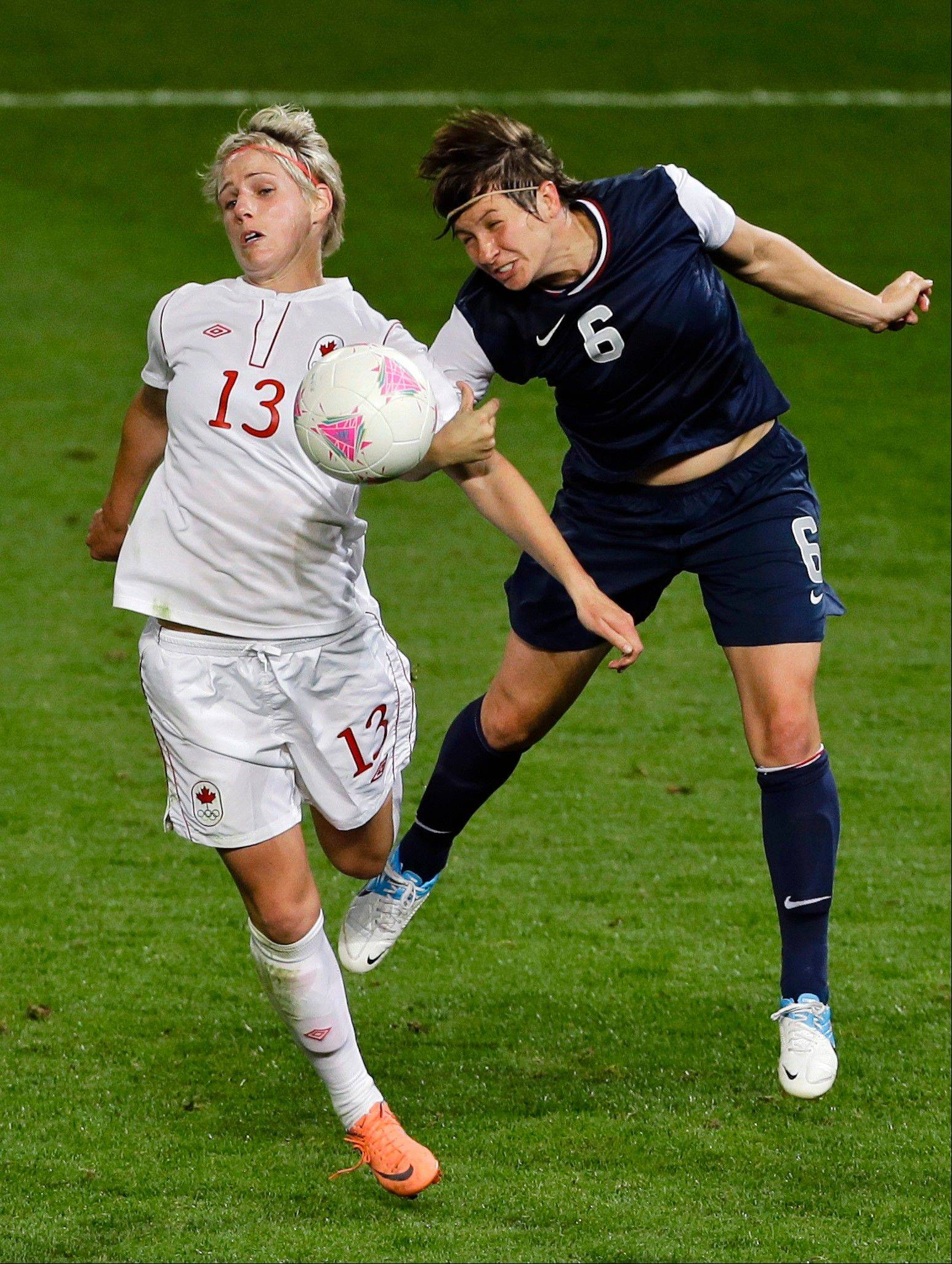 Team USA defender and Crystal Lake native Amy Le Peilbet, right, and Canada's Sophie Schmidt compete for the ball during Monday's Olympic semifinal match in Manchester, England.