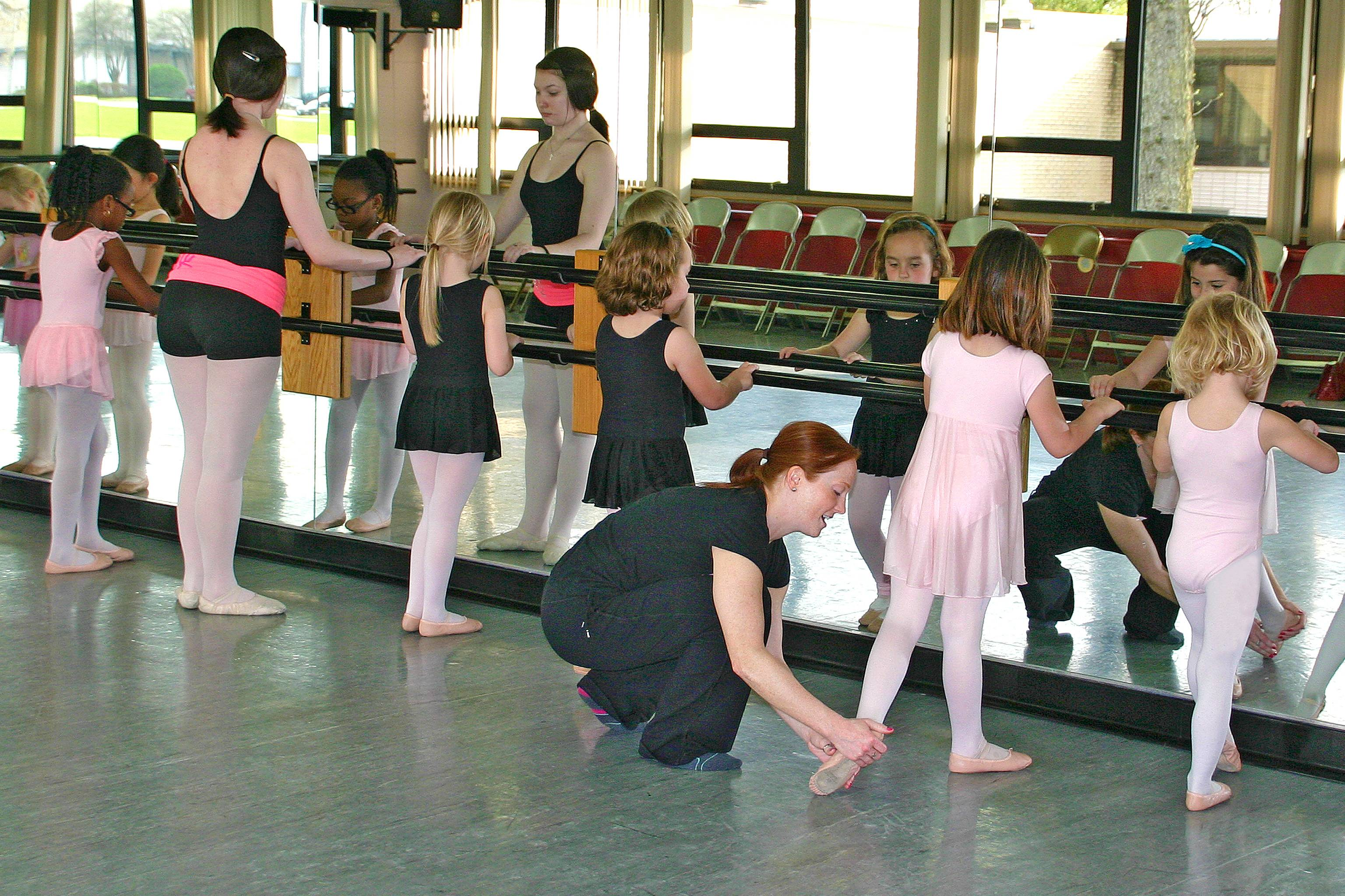 School of Dance Instructor Anne Gollenberg corrects a young ballerina's position at the School of Dance Open House