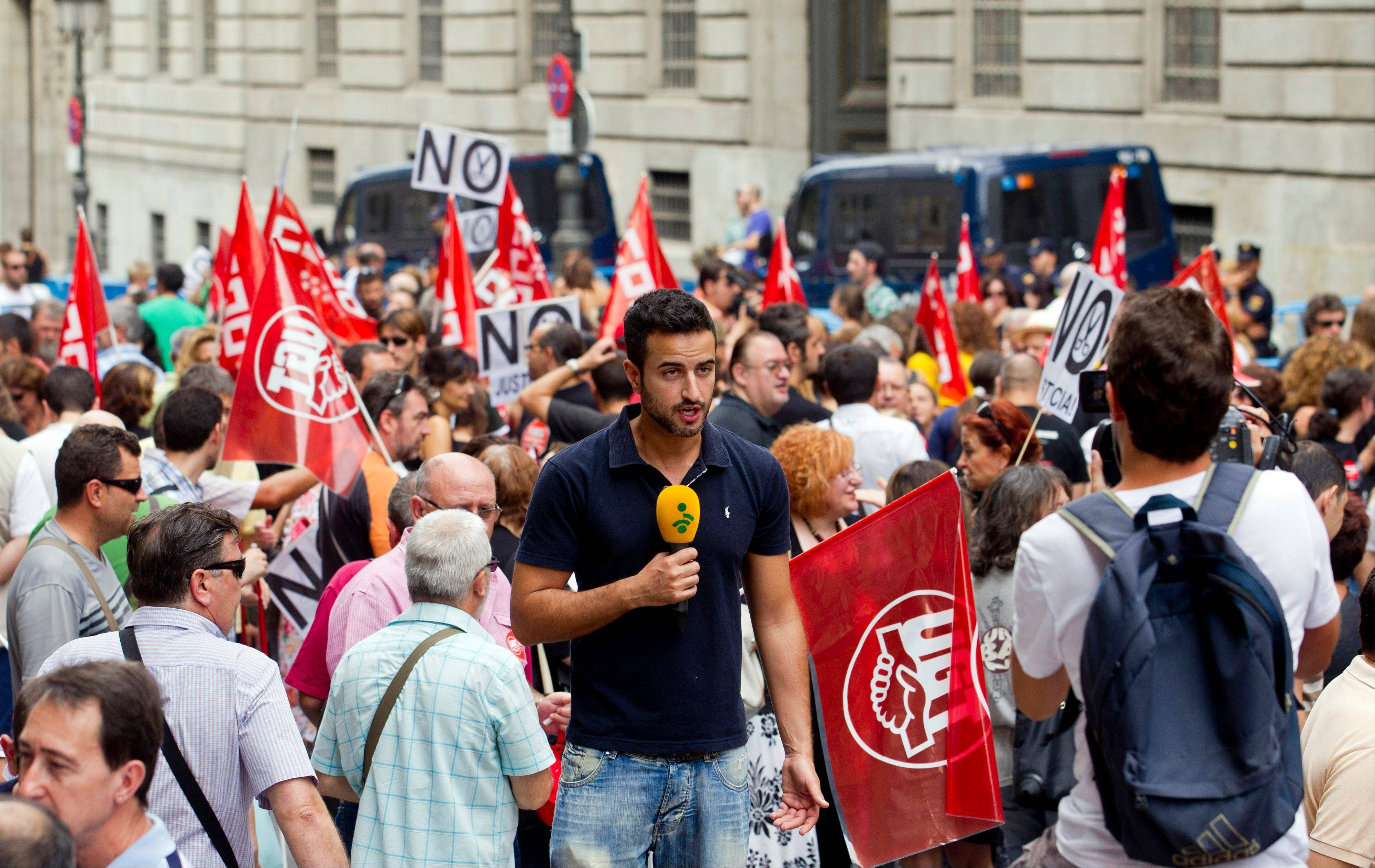 A television journalist reports from outside the Finance Ministry as civil servants protest, in Madrid, Friday