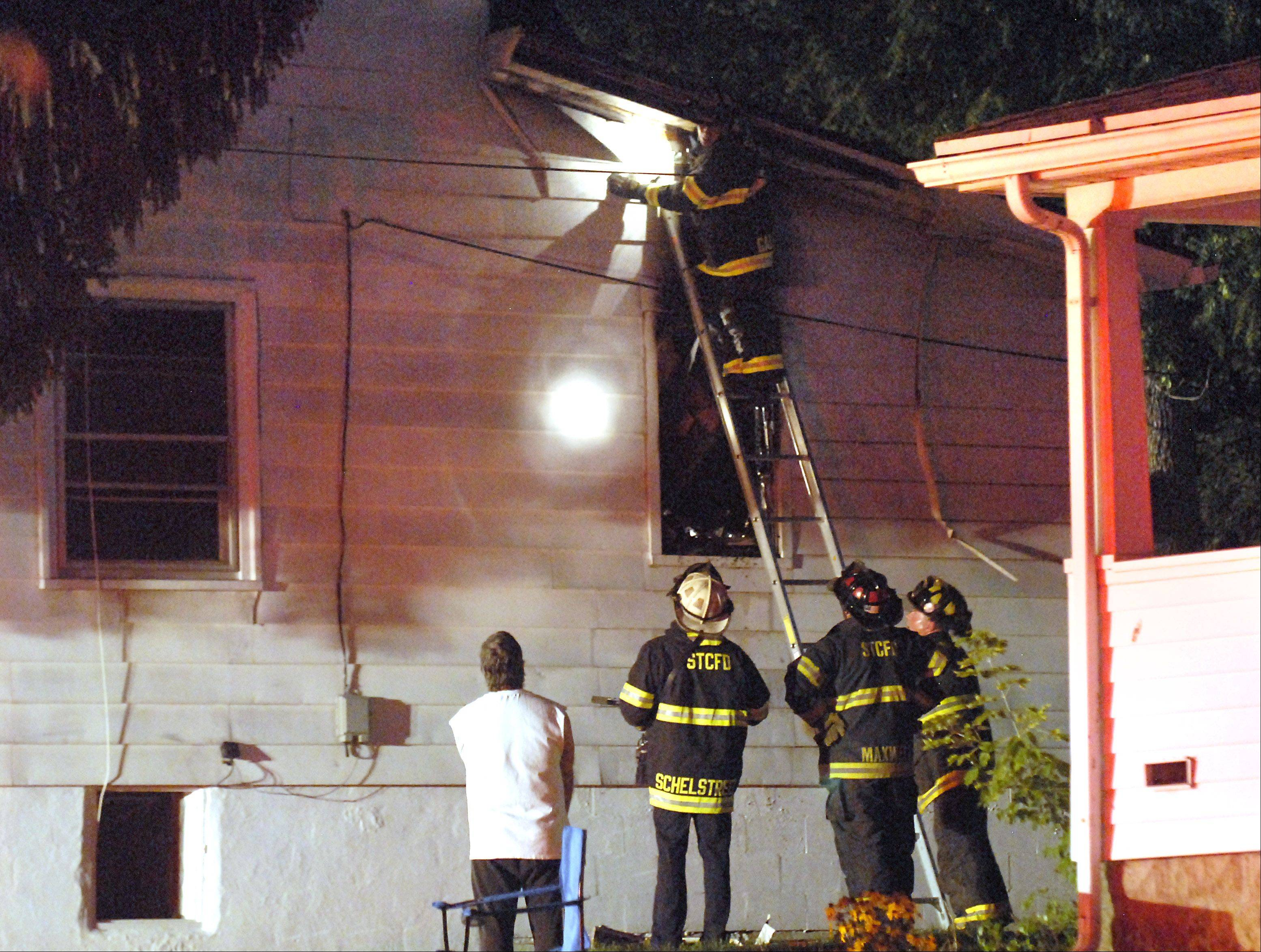 St. Charles firefighters check the roof after extinguishing a house fire on the 0-100 block of North 12th Street in St. Charles Friday night. Several fire departments � including St. Charles, Geneva, Batavia and South Elgin � responded to the fire, which was contained within 30 minutes. No injuries were reported, but the home was left uninhabitable.