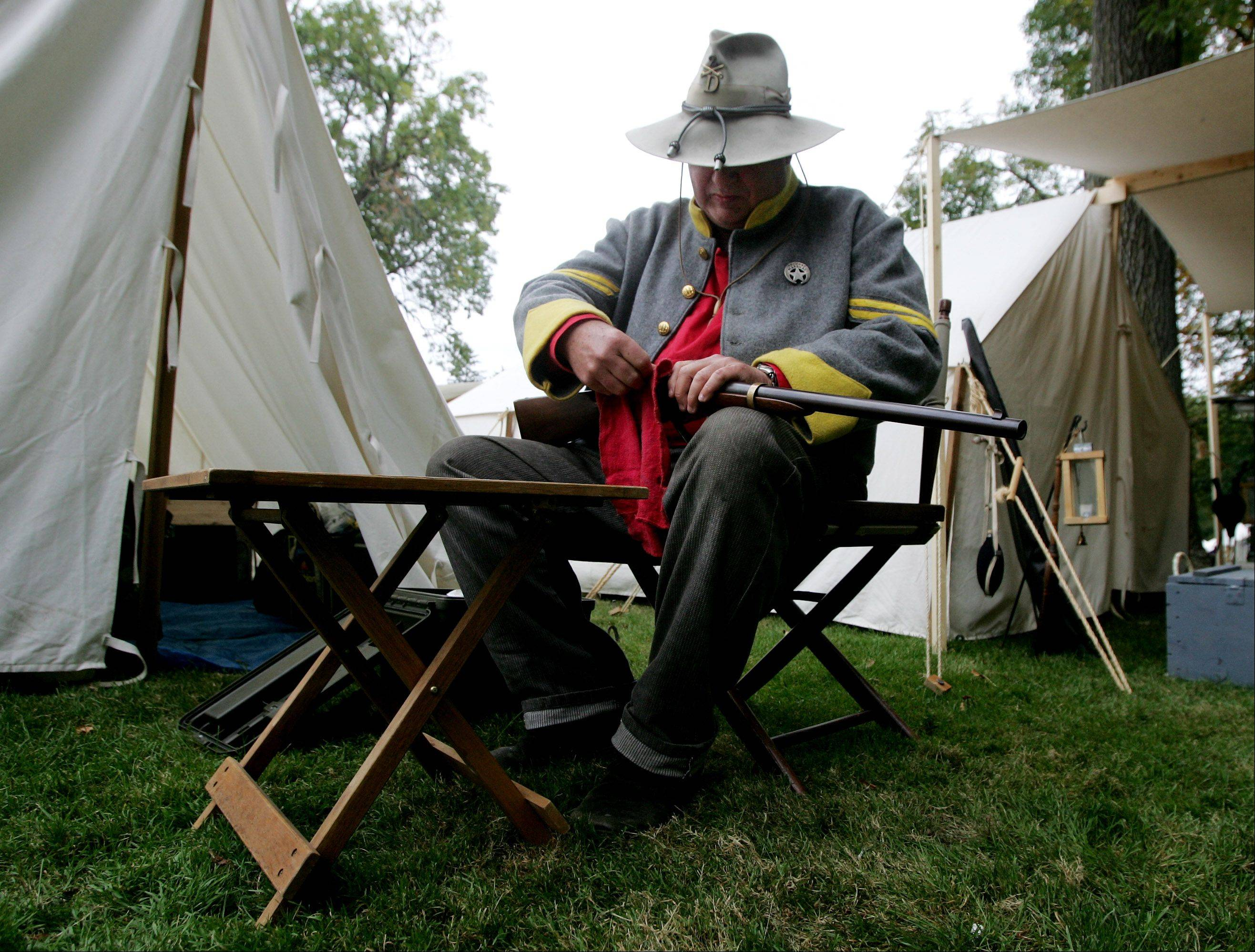 John Downey of Sussex, Wisconsin cleans a Sharp�s rifle during last year�s Annual Lake Villa Civil War Days Sunday at the Lehmann Mansion. Downey was an infantryman with the Confederate 2nd Kentucky Cavalry.