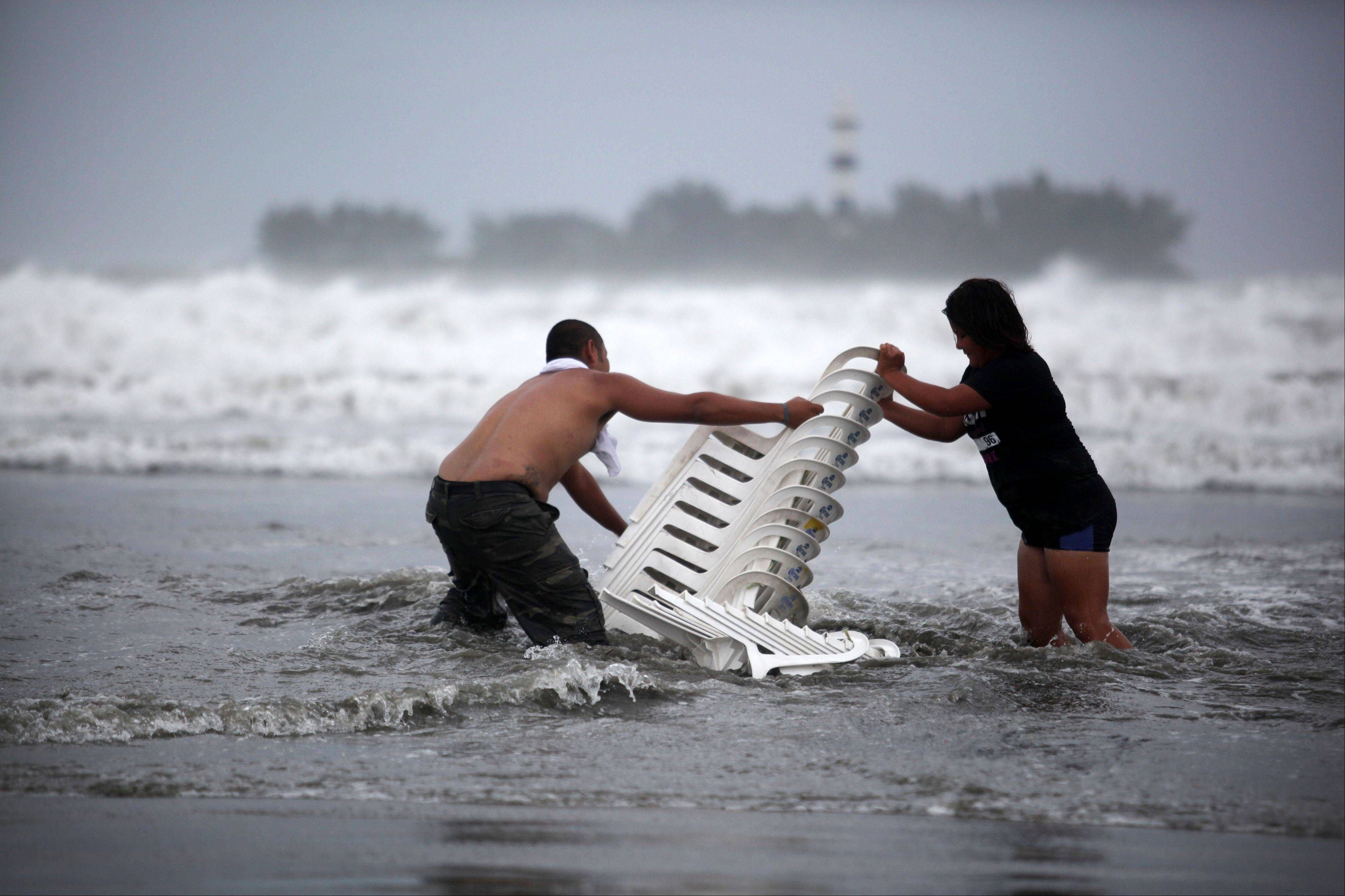 Vendors try to recover their chairs after high waves dragged their beach stalls into the sea in Veracruz, Mexico, Thursday Aug. 9, 2012. Tropical Storm Ernesto headed into Mexico's southern Gulf coast as authorities in the flood-prone region prepared shelters, army troops and rescue personnel for drenching rains.