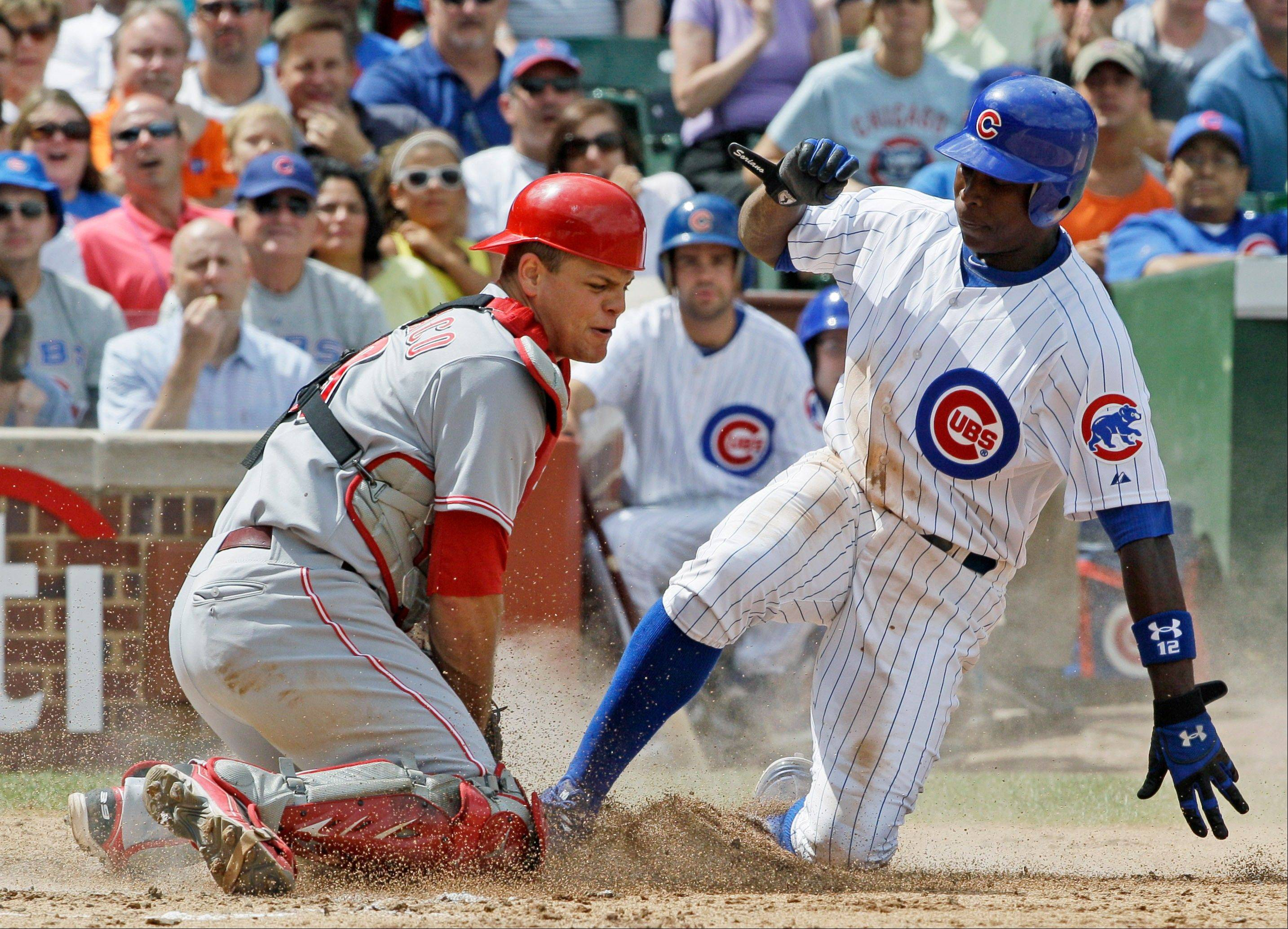 Reds catcher Devin Mesoraco, left, tags out Alfonso Soriano during the third inning of the Cubs� 10-8 loss to Cincinnati on Friday at Wrigley Field.
