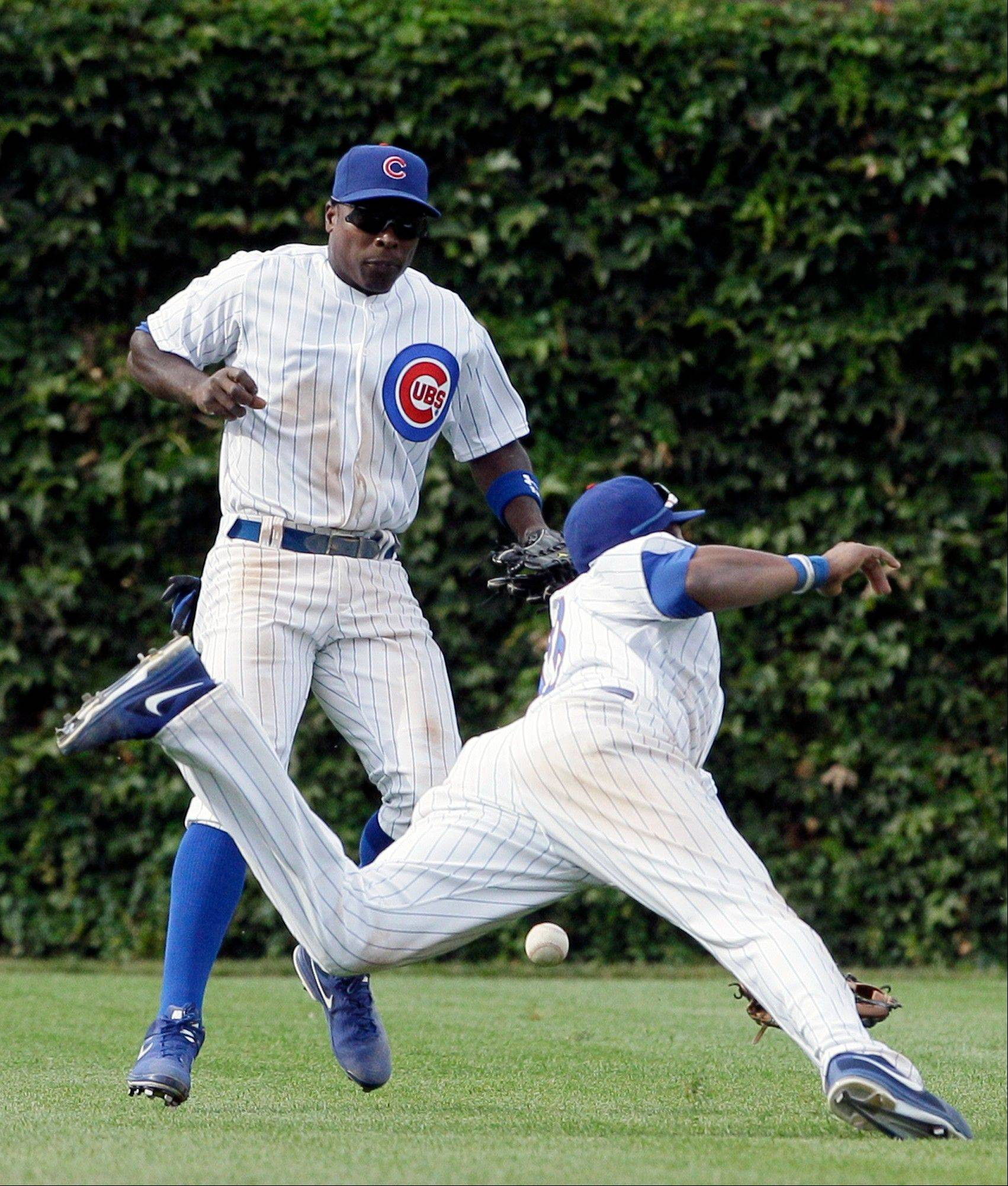 Alfonso Soriano, left, and Starlin Castro can't make a play on a single hit by the Reds' Brandon Phillips during the ninth inning Friday at Wrigley Field.
