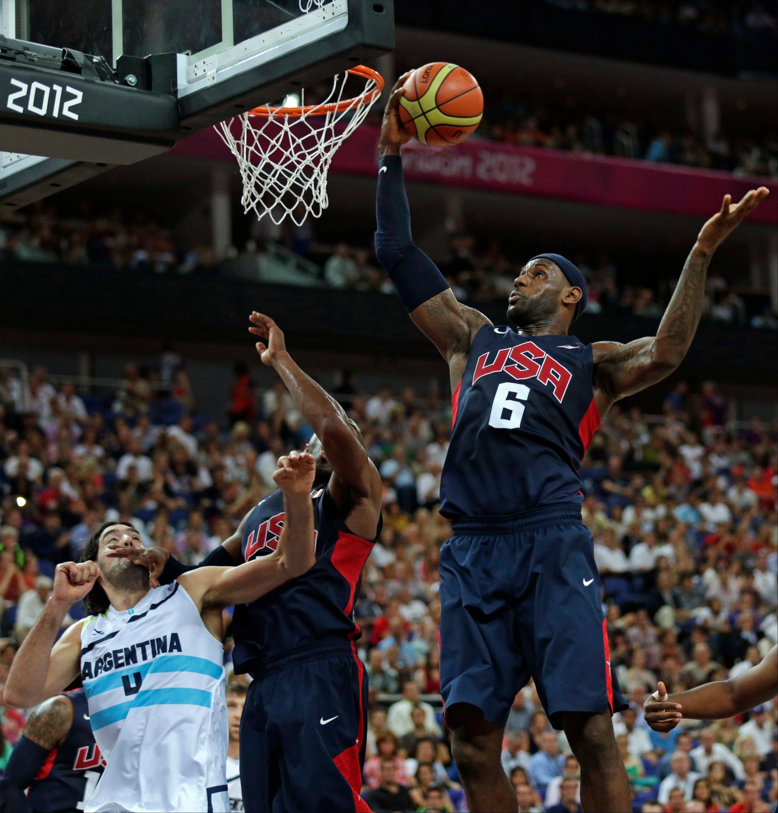 United States forward LeBron James, right, grabs a rebound as teammate Kobe Bryant blocks out Argentina's Luis Scola Friday during the semifinals.