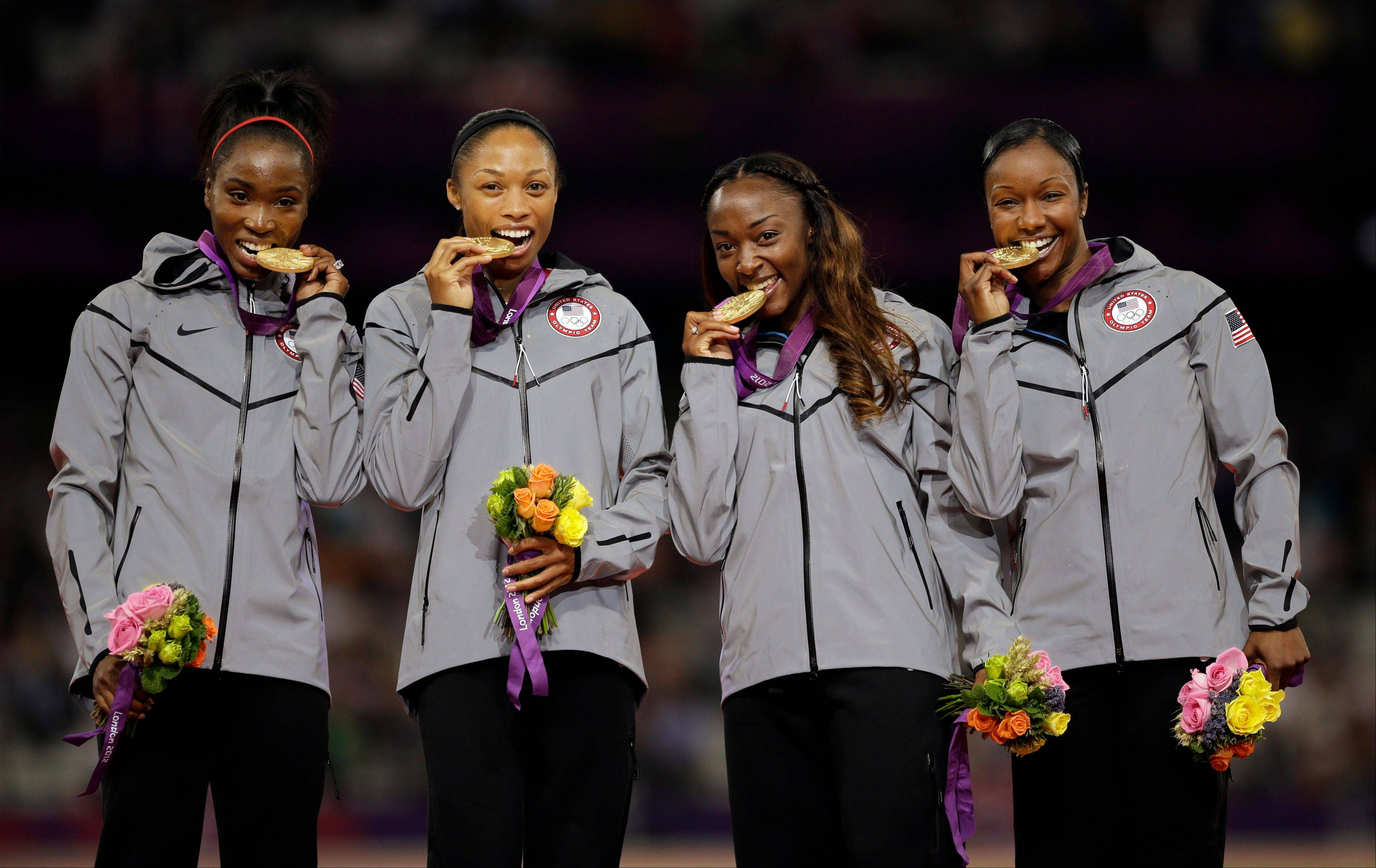 USA sprinters Tianna Madison, Allyson Felix, Bianca Knight and Carmelita Jeter celebrate their gold medal win Friday. Midway through Friday's events, the Americans led China in total medals, 90 to 81, and golds, 40 to 37.