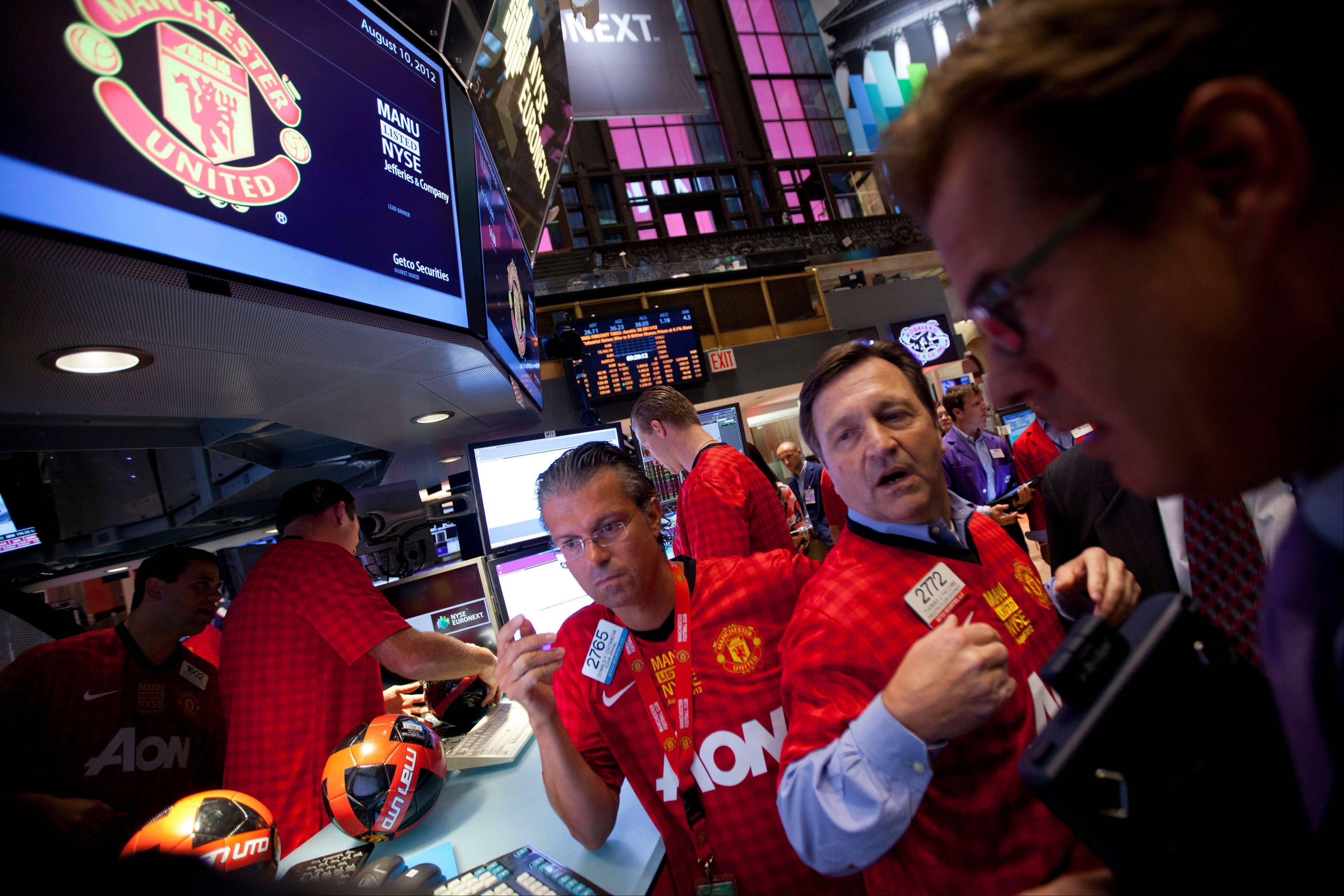 Traders work while wearing Manchester United jerseys on the floor of the New York Stock Exchange on Friday, Aug. 10, 2012 in New York. Shares of soccer club Manchester United made their public debut Friday, edging up slightly as shareholders' enthusiasm for the celebrated team was offset by worry about its debt load and financial performance.