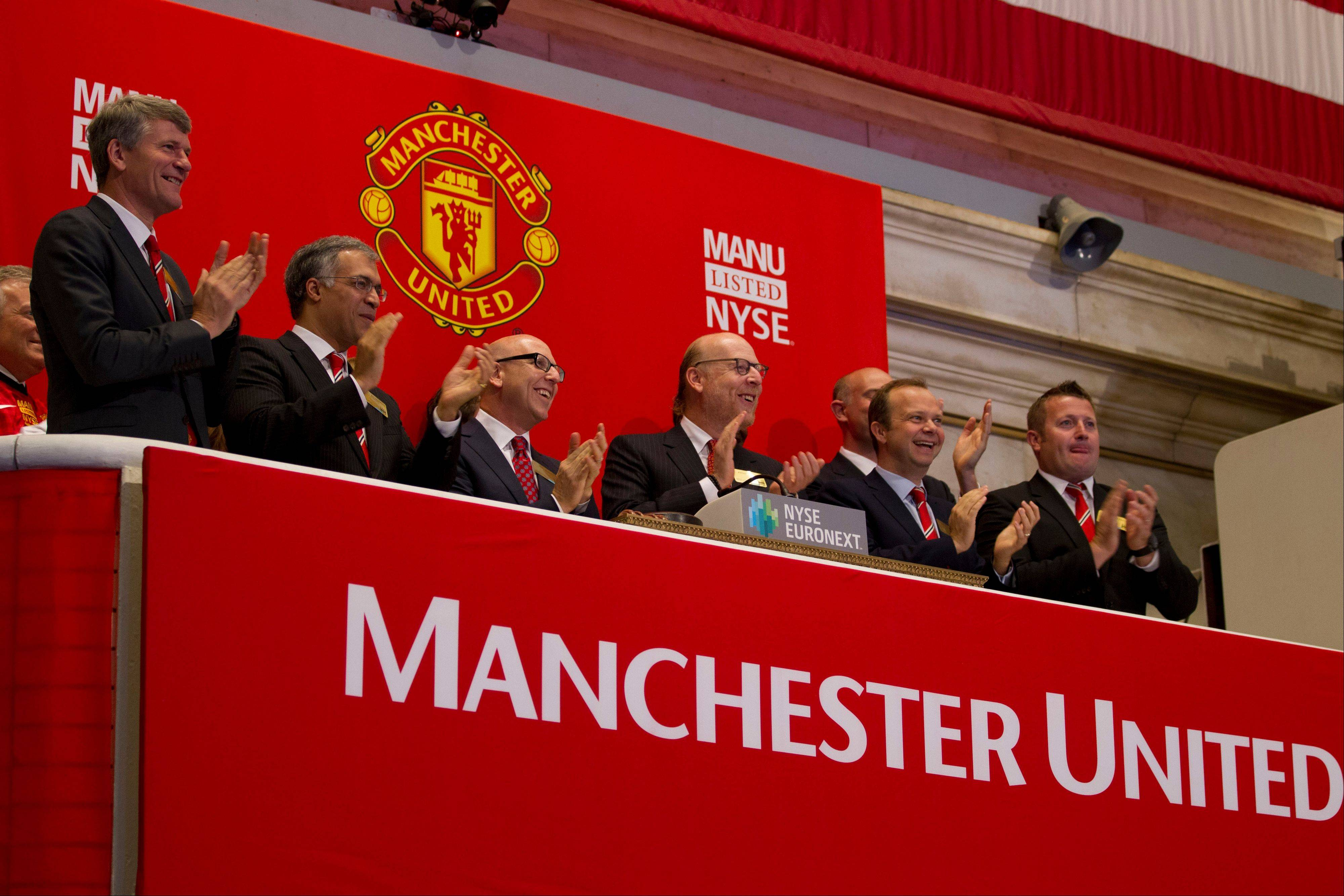 Executives from Manchester United, including Avram Glazer, fourth from left, and Joel Glazer, third from left, applaud after ringing the opening bell at the New York Stock Exchange on Friday, Aug. 10, 2012 in New York. Shares of soccer club Manchester United made their public debut Friday, edging up slightly as shareholders' enthusiasm for the celebrated team was offset by worry about its debt load and financial performance.