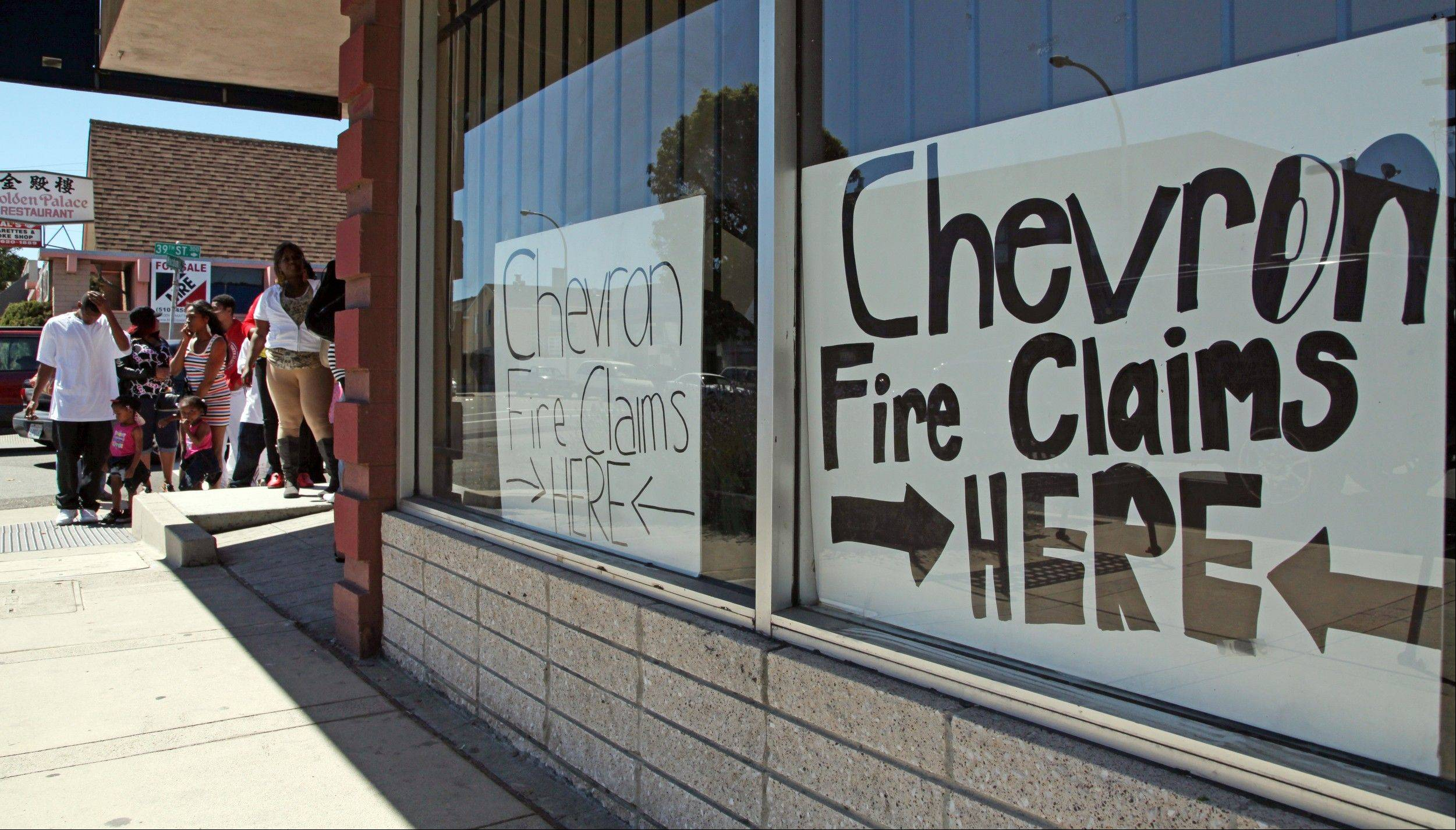 Area residents line up outside the injury attorney offices of R. Nicholas Haney in Richmond, Calif., on Tuesday, Aug. 7, 2012, to pick up a claim form in response to the Chevron refinery fire that impacted the community. Investigators are waiting for access to the charred crude oil unit of a Chevron refinery where a fire sent a towering plume of black smoke into San Francisco Bay area skies and pushed gas prices higher along the West Coast. Hundreds of people went to hospitals with respiratory issues during the fire at the Richmond refinery that produces 16 percent of the region's daily gasoline supply.