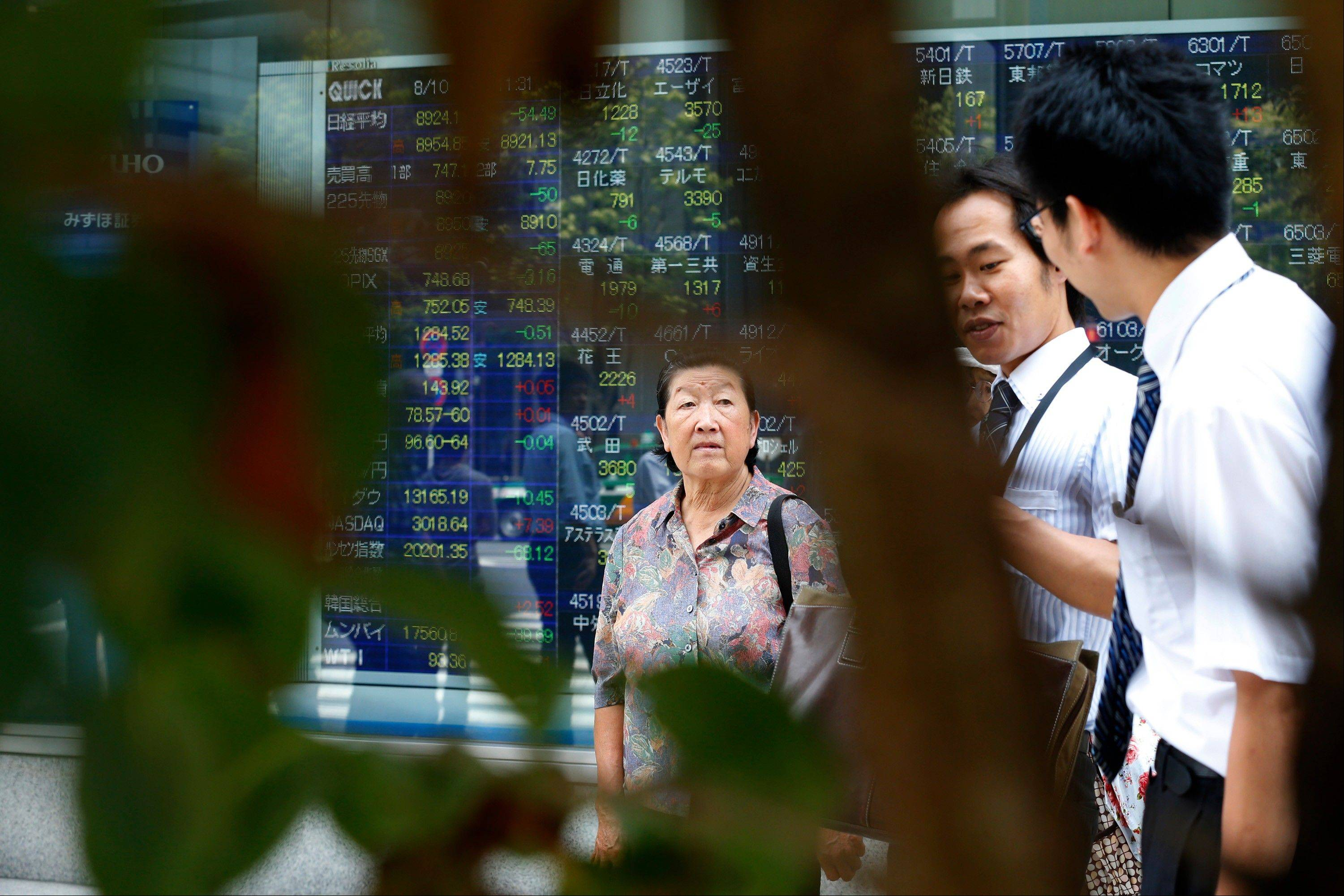 People walk past an electronic stock indicator in Tokyo, Friday.