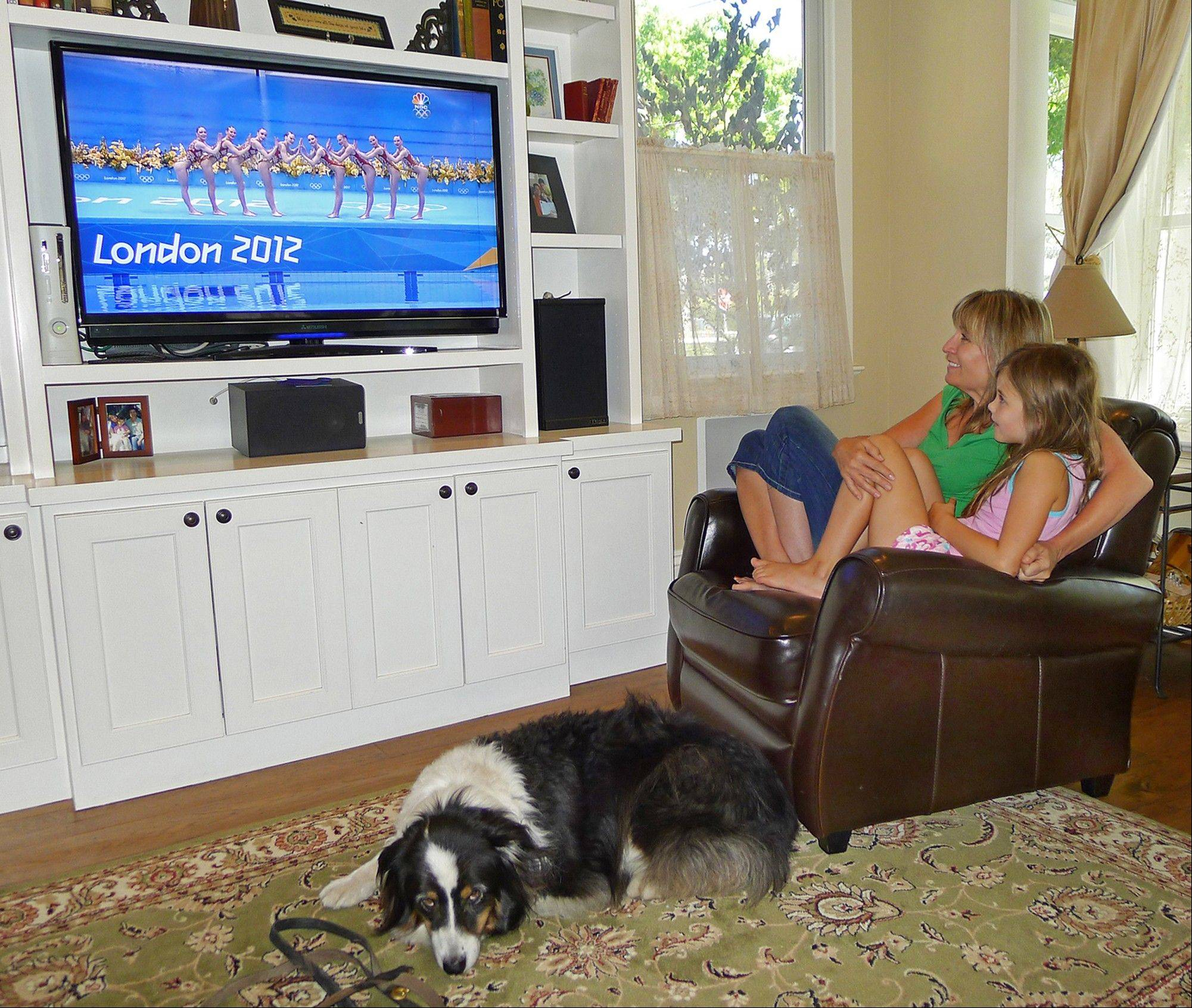 "Julie O'Grady watches the 2012 Olympics with her daughter Molly and dog Bosco Thursday in her home in Palo Alto, Calif. If Bosco, Julie O'Grady's Australian shepherd in Palo Alto, Calif., could speak, he'd likely be shrieking, ""Get a grip woman!"" His pained, pathetic pleas haven't been enough to pry the tech industry public relations specialist away from the Olympics. Nearly eight in 10 Americans, have watched or followed the games either on television, online or via social networks, according to a survey done Aug. 2-5 by the Pew Research Center for the People & the Press."