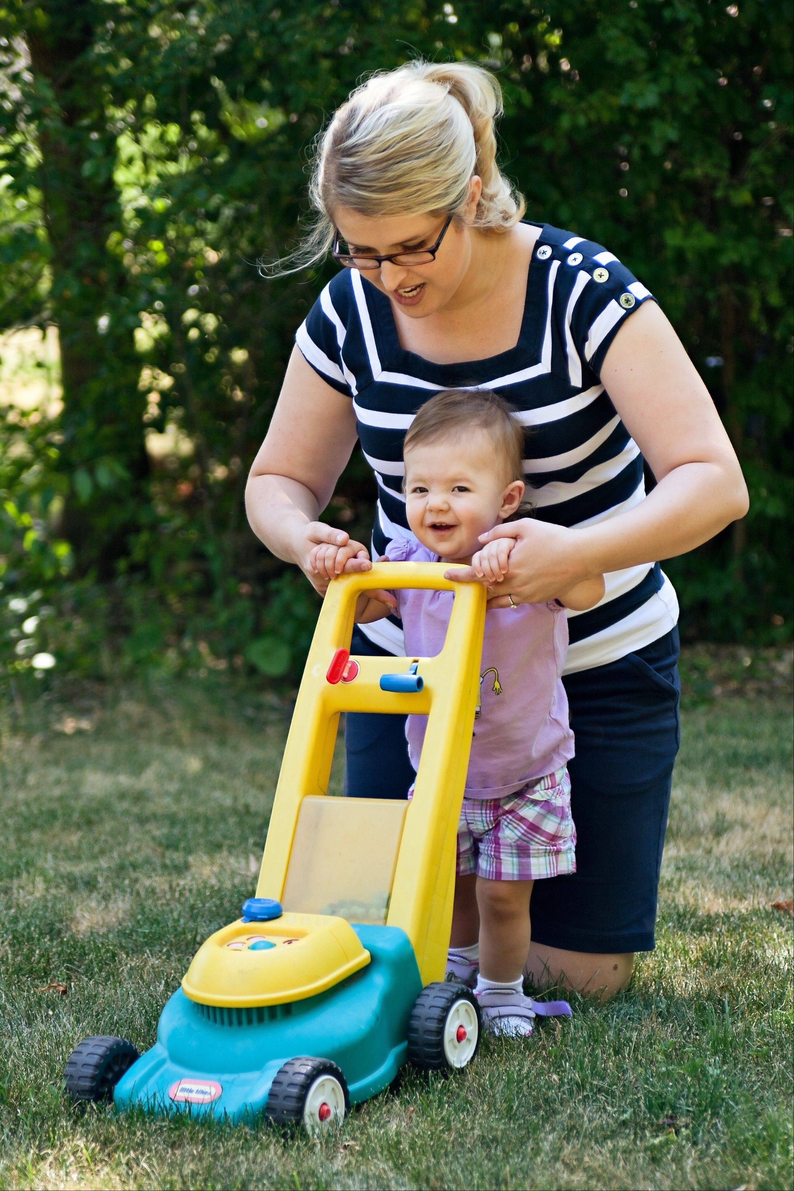 Julie Jancius helps her 15-month-old daughter Ellie play with her toy lawn mower.