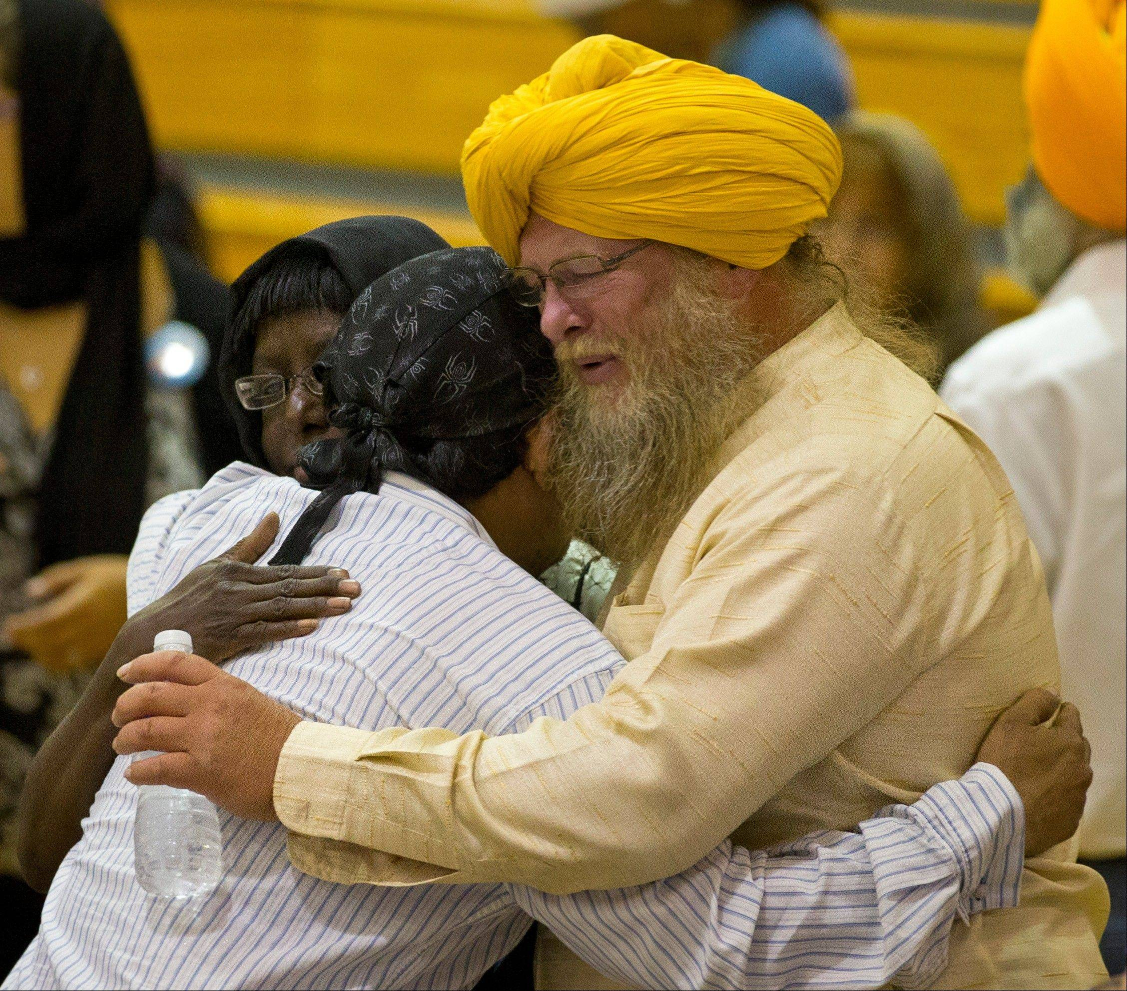 Associated Press Mourners console one another Friday at the public service held in the Oak Creek High School.
