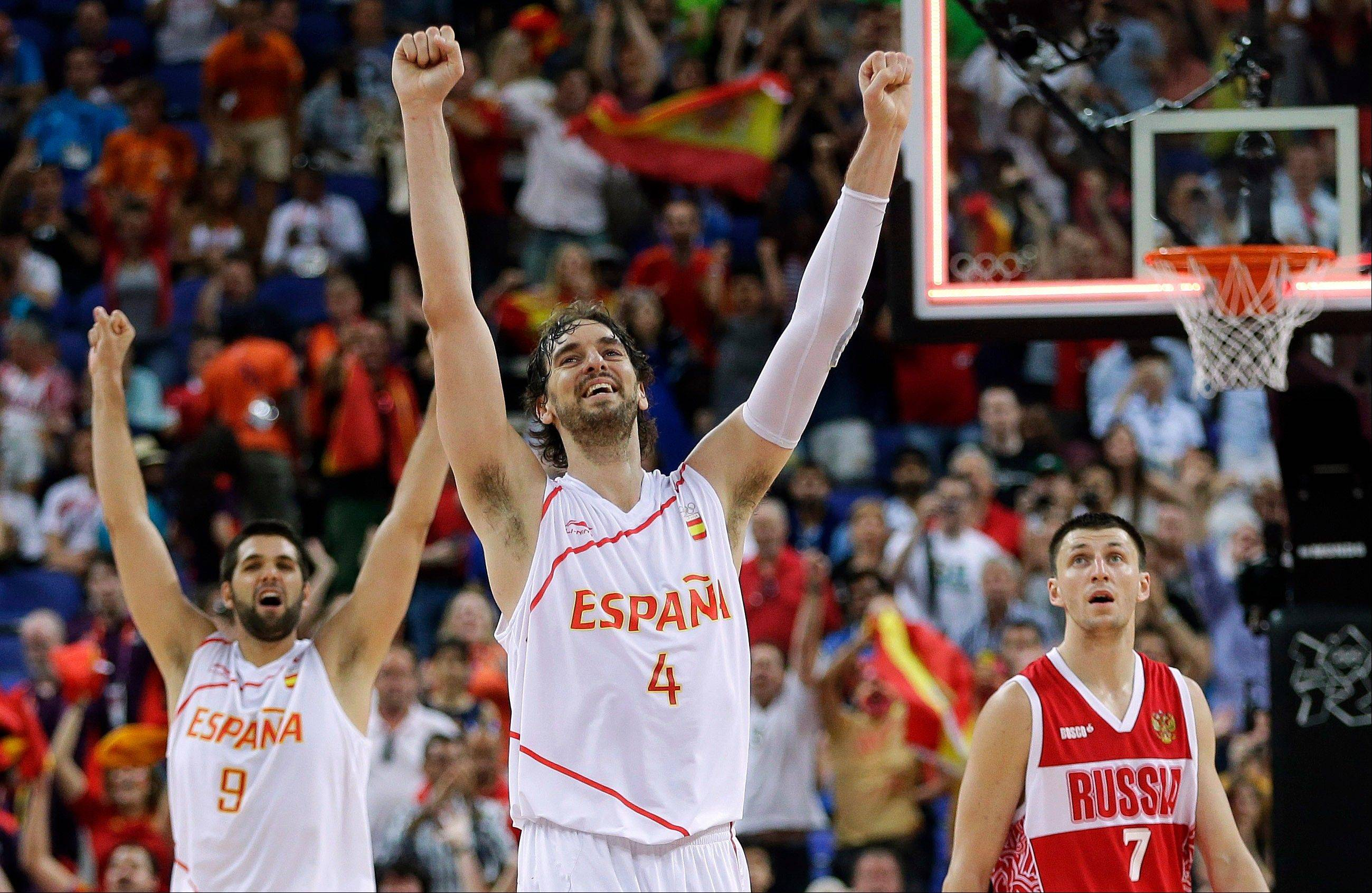 Spain's Pau Gasol (4) and teammate Felipe Reyes (9) celebrate their win over Russia in a semifinal men's basketball game at the 2012 Summer Olympics, Friday, Aug. 10, 2012, in London. Russia's Vitaliy Fridzon is at right.