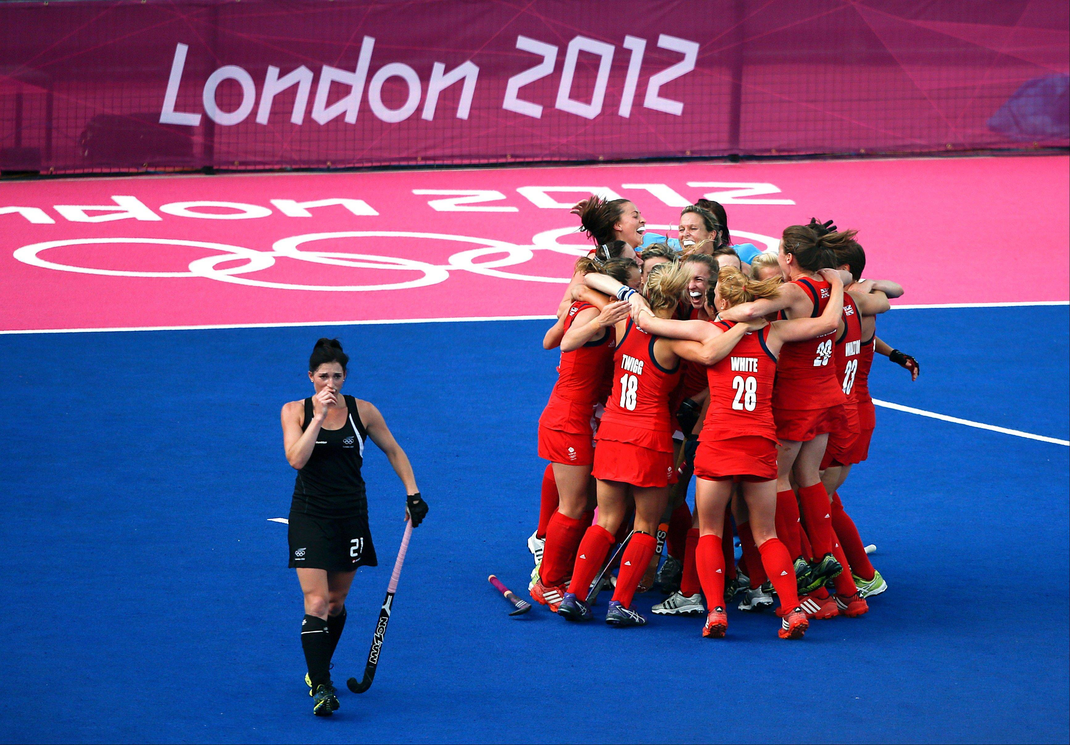New Zealand's Cathryn Finlayson, left, walks off the field as Britain's hockey players celebrate their 3-1 win in a women's field hockey bronze medal match at the 2012 Summer Olympics, London, Friday, Aug. 10, 2012.