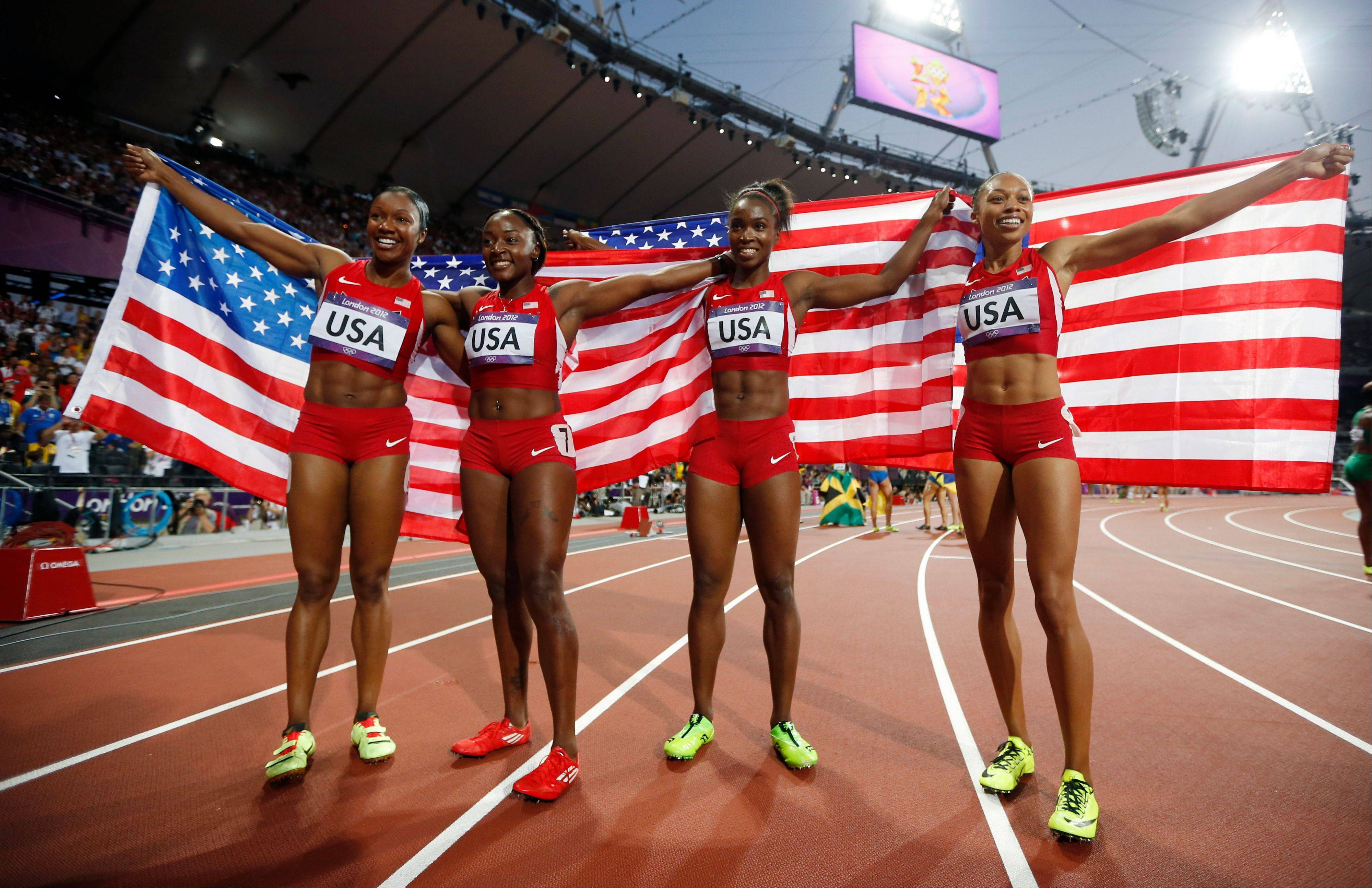 United States' women's 4 x100-meter relay team members, from left, Carmelita Jeter, Bianca Knight, Tianna Madison and Allyson Felix, celebrate their gold medal win during the athletics in the Olympic Stadium at the 2012 Summer Olympics, London, Friday, Aug. 10, 2012. The United States relay team set a new world record with a time of 40.82 seconds