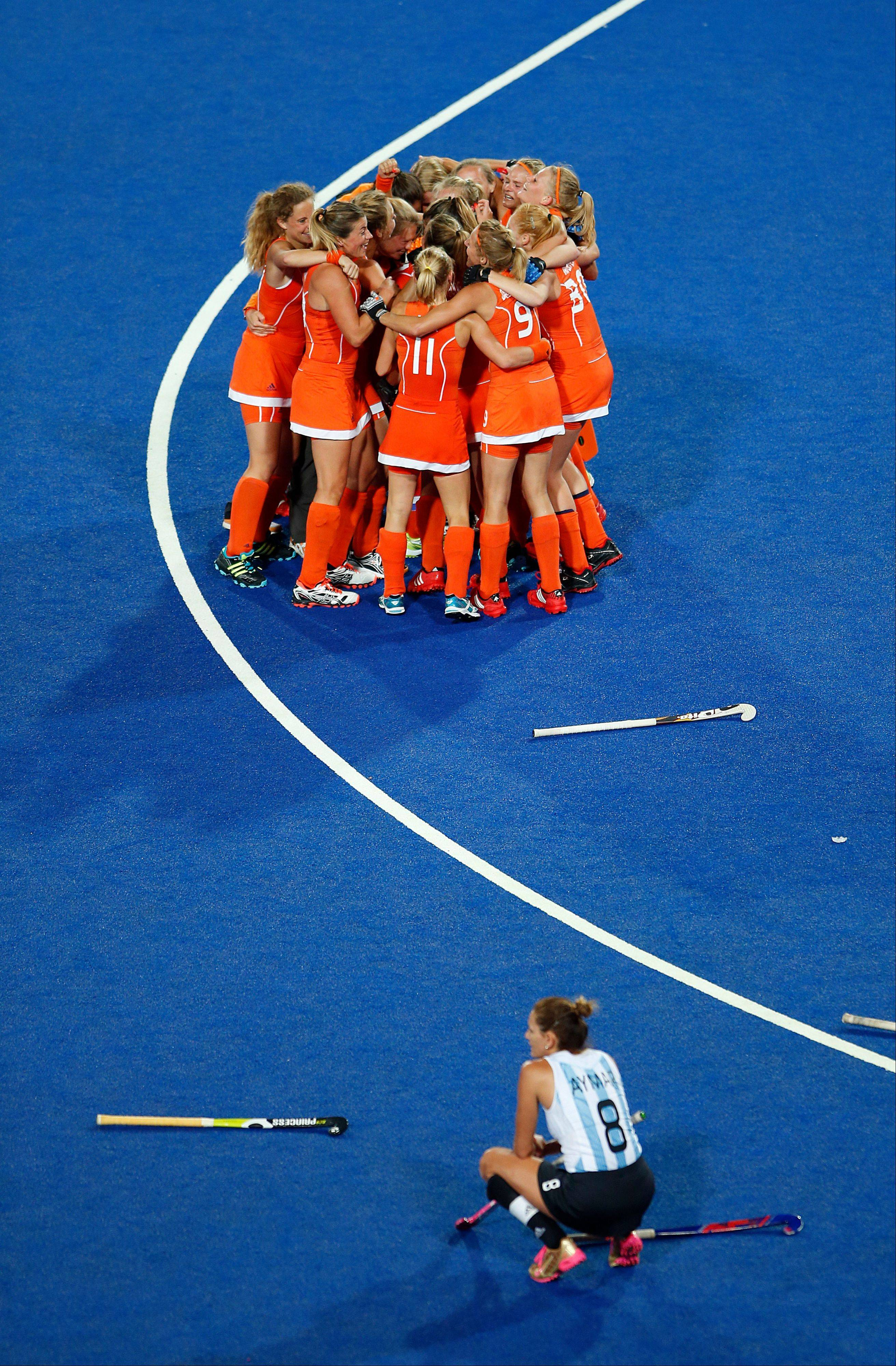 Argentina's Luciana-Aymar, bottom, looks on as Netherlands hockey players celebrate their win in a women's hockey gold medal match at the 2012 Summer Olympics, London, Friday, Aug. 10, 2012.