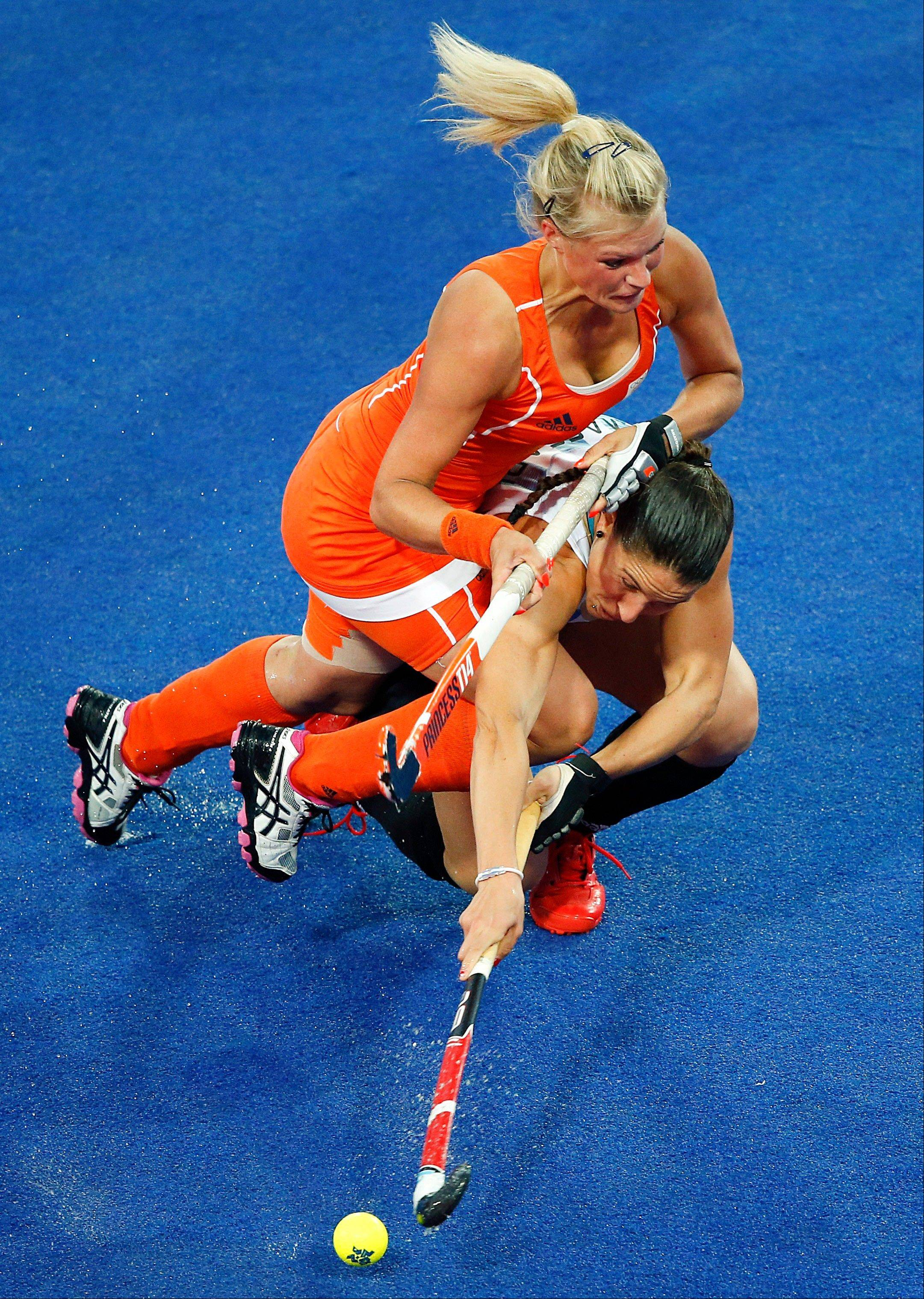 The Netherlands' Sophie Polkamp, top, and Argentina's Sofia Maccari fight for the ball during a women's hockey gold medal match at the 2012 Summer Olympics, London, Friday, Aug. 10, 2012.