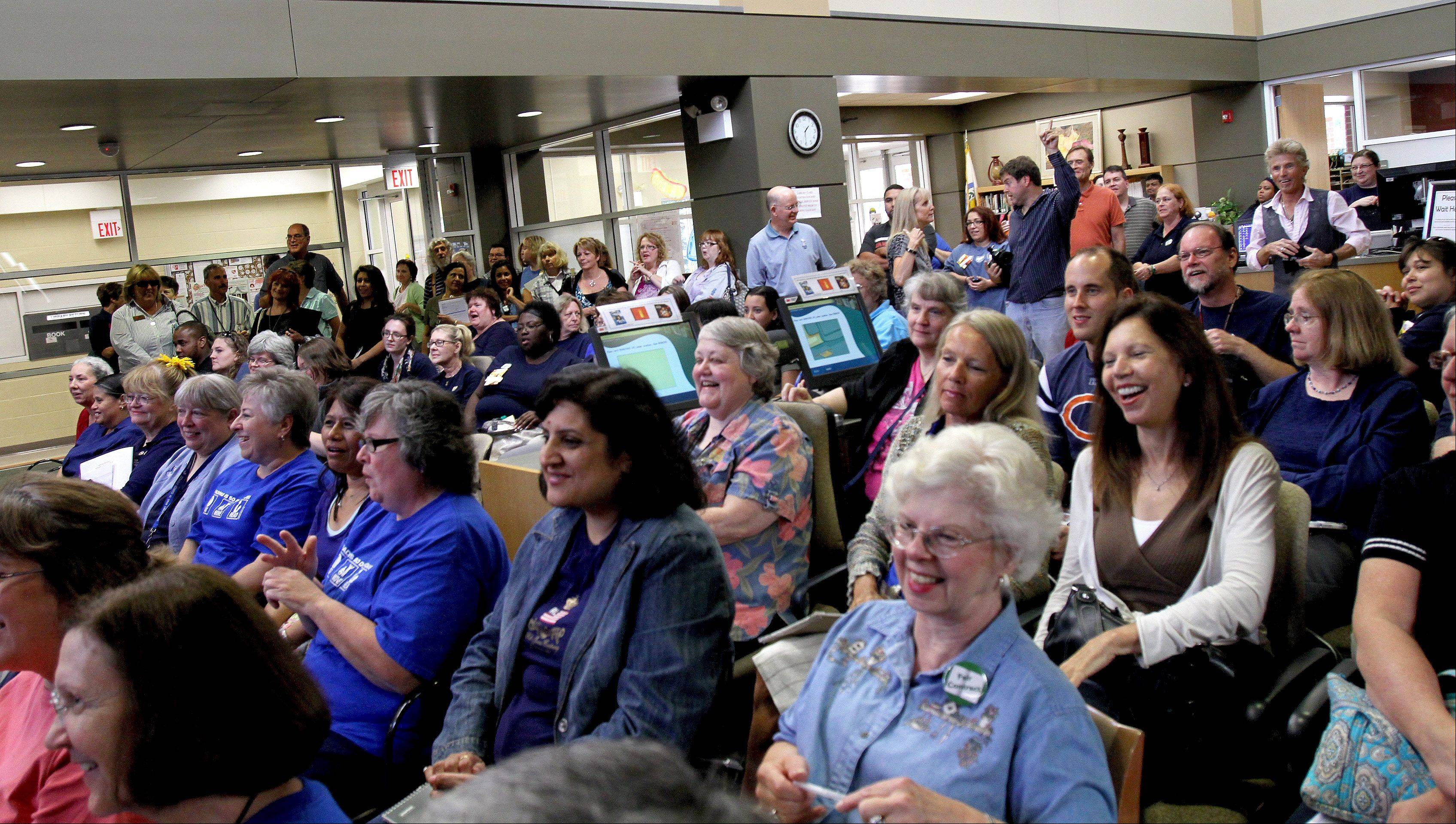 Library employees enjoy a mini-concert by musician Jim Peterik during his visit Friday to the Eola Road Branch Library in Aurora.