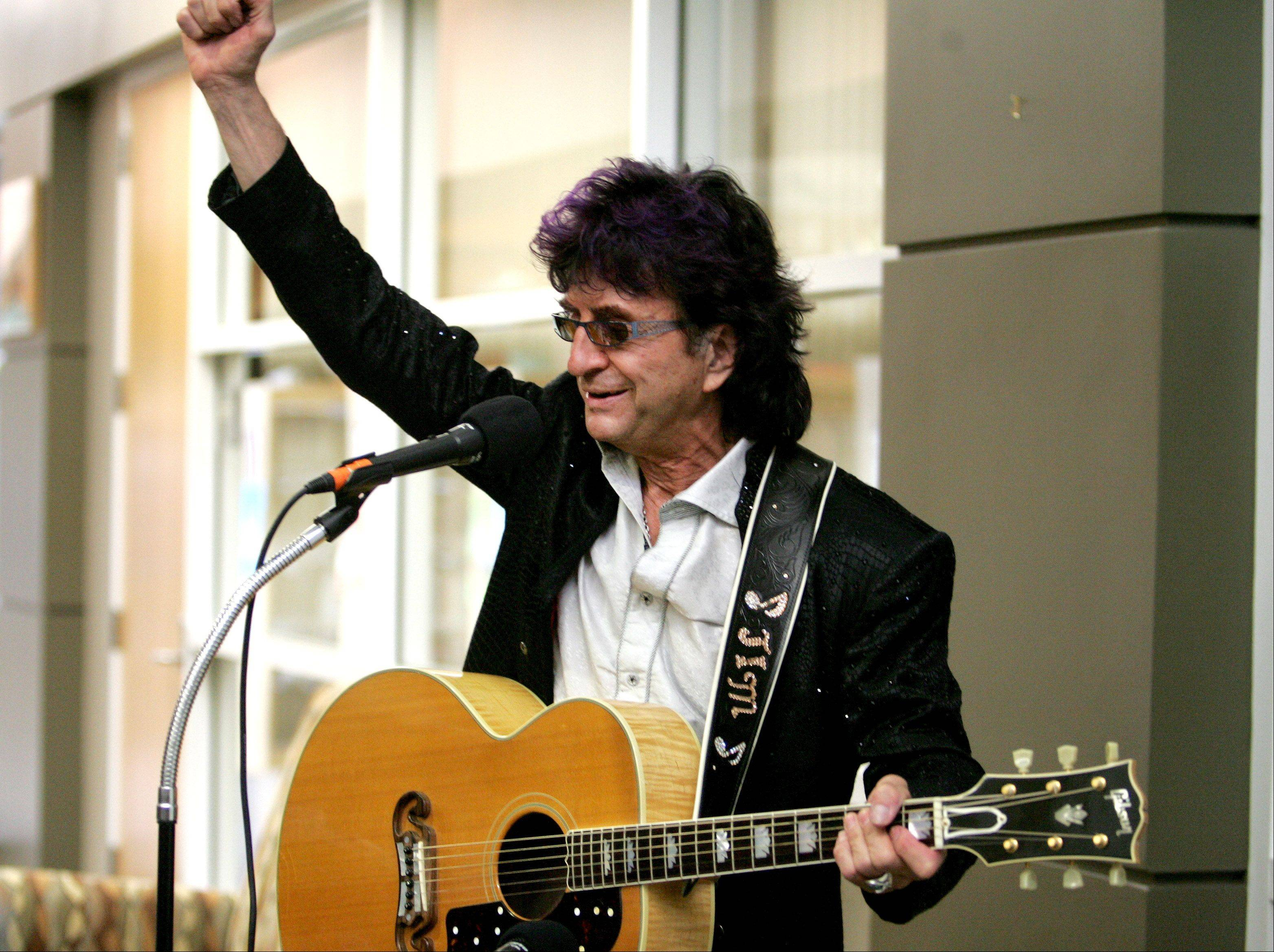 "Jim Peterik visits the Eola Road Branch Library in Aurora on Friday. He sang ""Eye of the Tiger"" for employees and shot scenes for the music video of his new song, ""Delusional."""