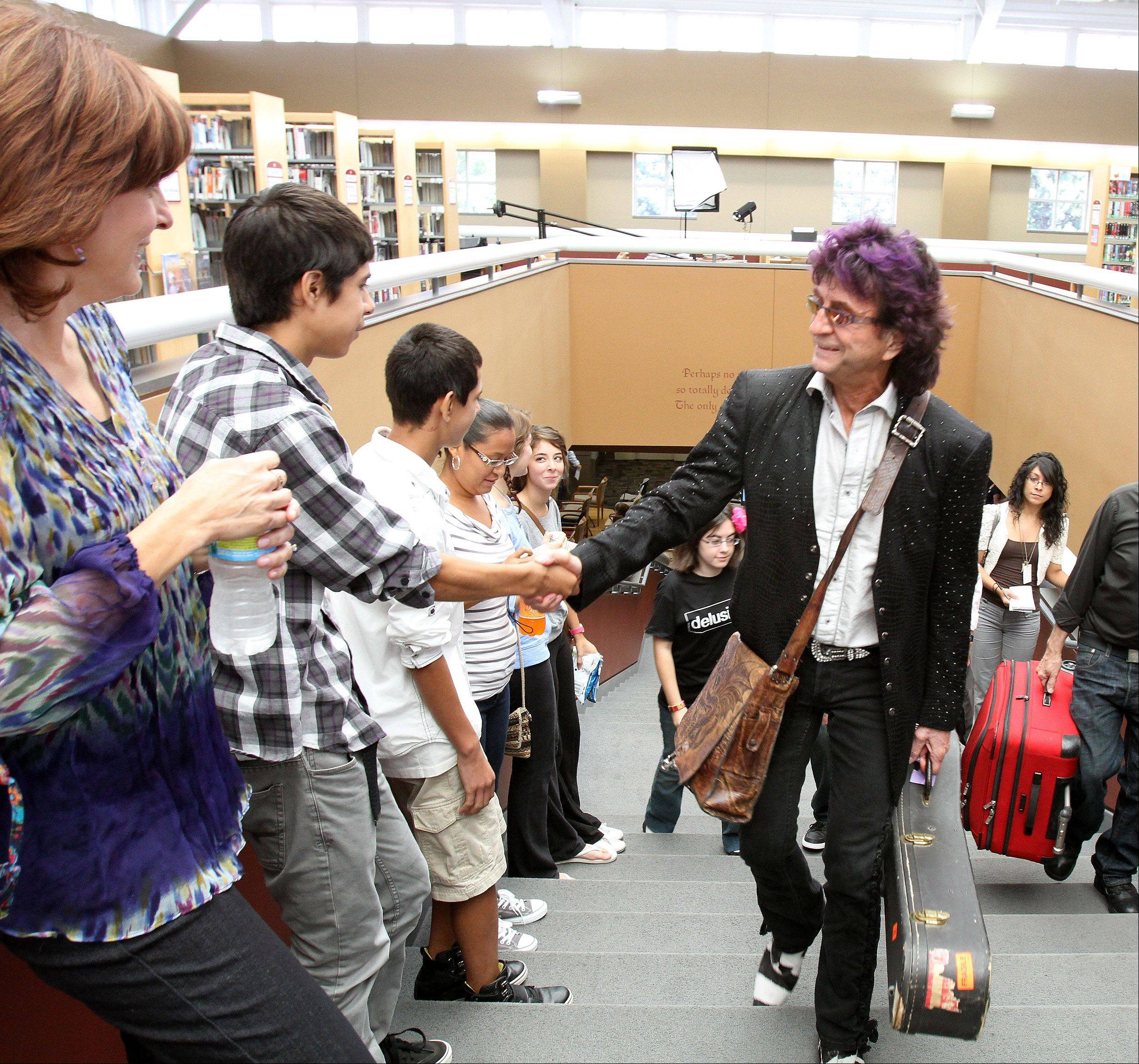 "Jim Peterik greets Jesus Cepeda, who was an extra in the music video for his new song, ""Delusional,"" as he visits the Eola Road Branch Library in Aurora. ""I love to mentor young talent,"" Peterik said. ""Sometimes I wish that I had someone to mentor me."""