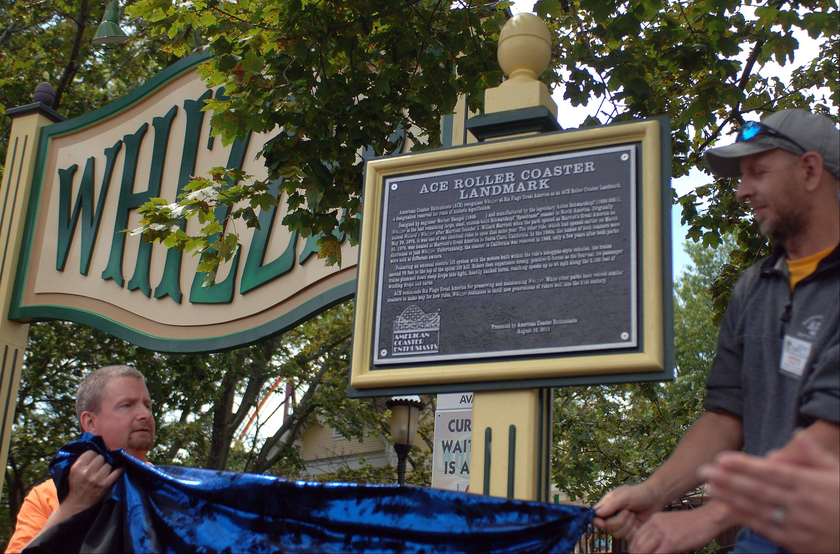 American Coaster Enthusiasts representatives Jeff Peters, of Salem, Wis., left, and Scott Heck, of Sheboygan, Wis., unveil the landmark plaque Friday near the Whizzer's entrance at Six Flags Great America in Gurnee.