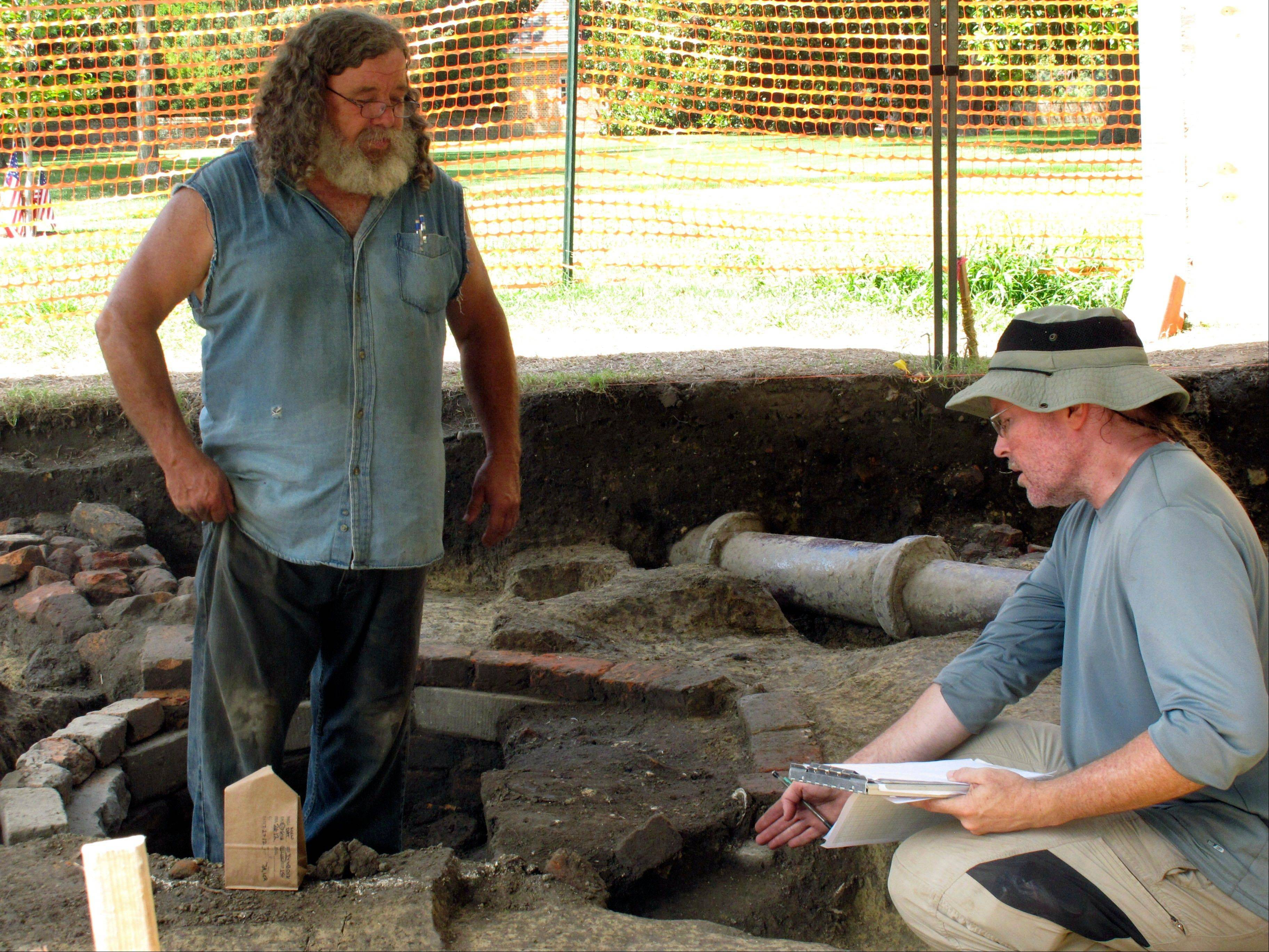 ASSOCIATED PRESS Archaeologists Kevin Goodrich, right, and Jack Aube, left, of the William and Mary Center for Archaeological Research, examine a well dug on the campus by Union troops during the Civil War.