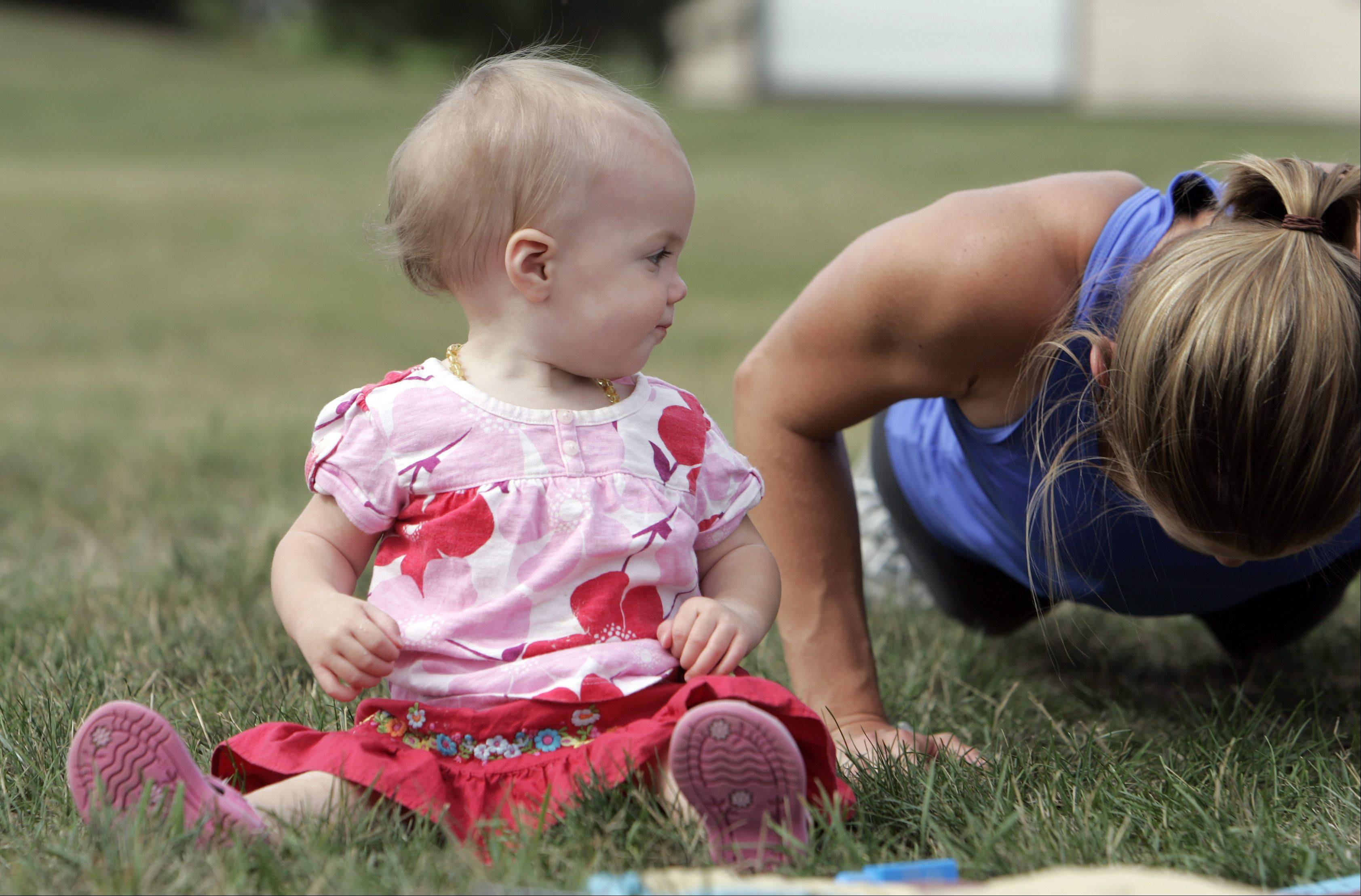 Emily Sobacki of Lake in the Hills, gets in some push-ups at Town Center Park in Gilberts as 11-month-old Skylar Guge of Gilberts watches with curiosity.