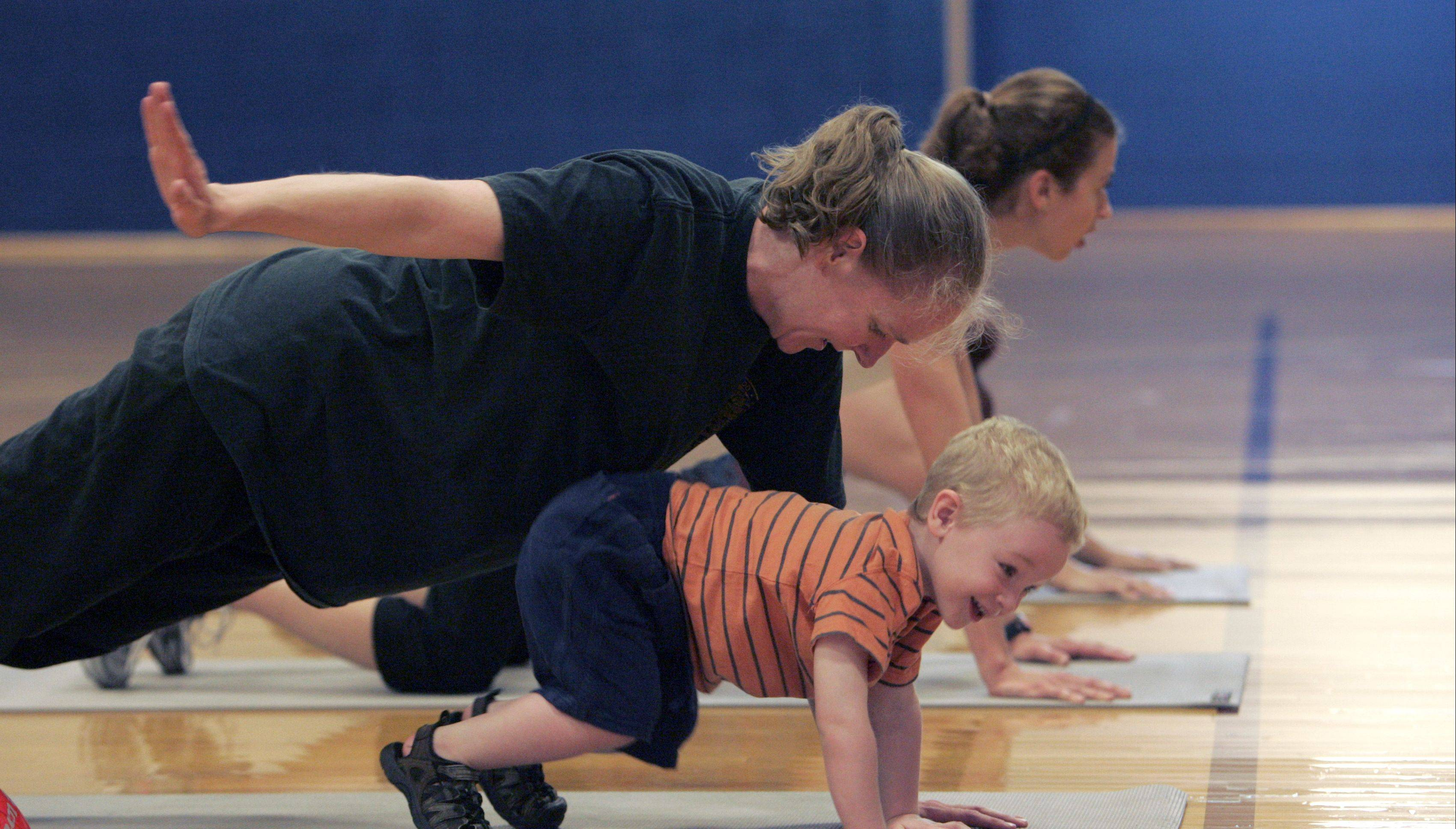 Erin Shaw of Elgin and her son Elijah, 5, share a giggle as they both try their hand at push-ups.