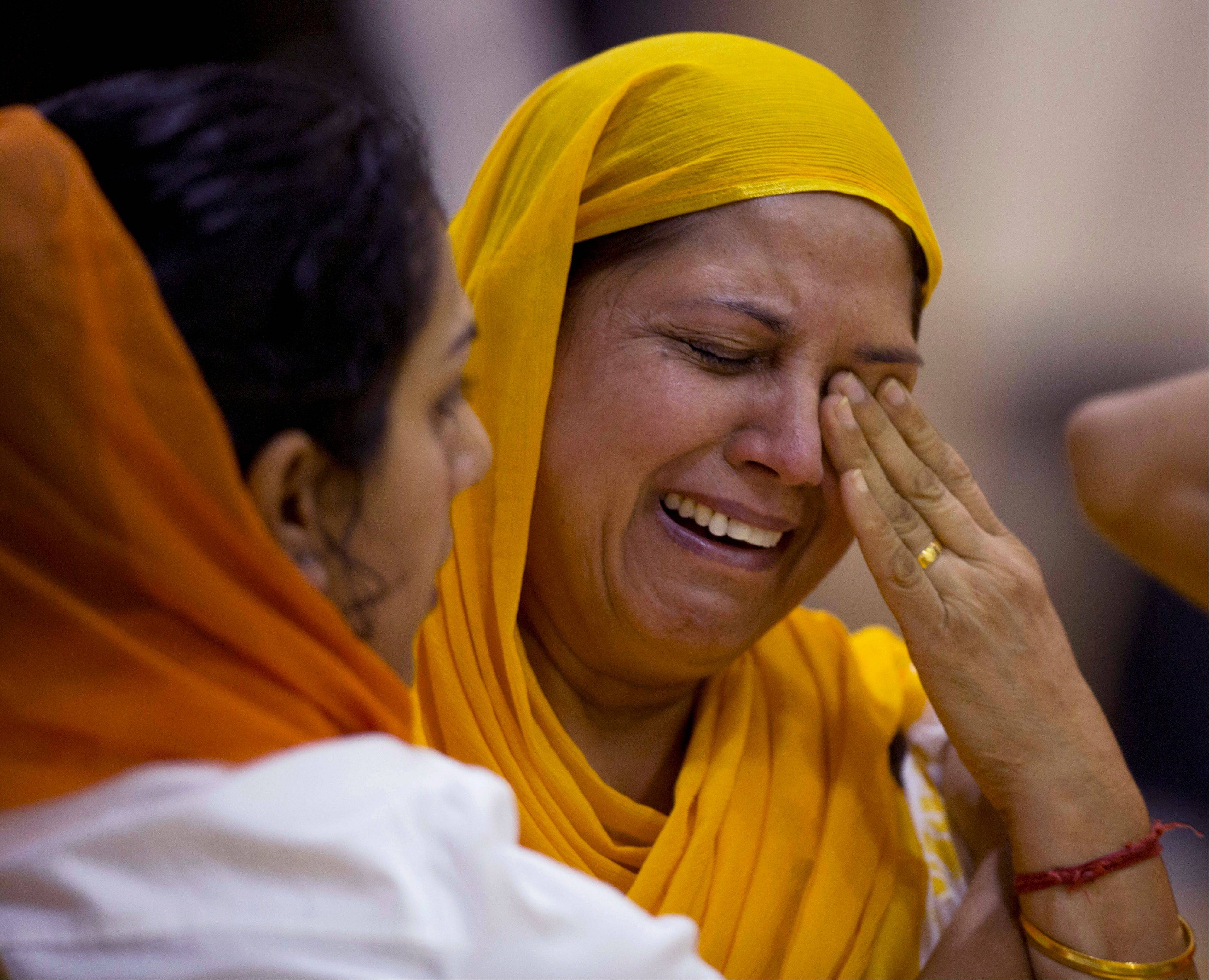 Mourners weep at the funeral and memorial service for the six victims of the Sikh temple of Wisconsin mass shooting in Oak Creek, Wis., Friday, Aug 10, 2012. The public service was held in the Oak Creek High School. Three other people were wounded in the shooting last Sunday at the temple.