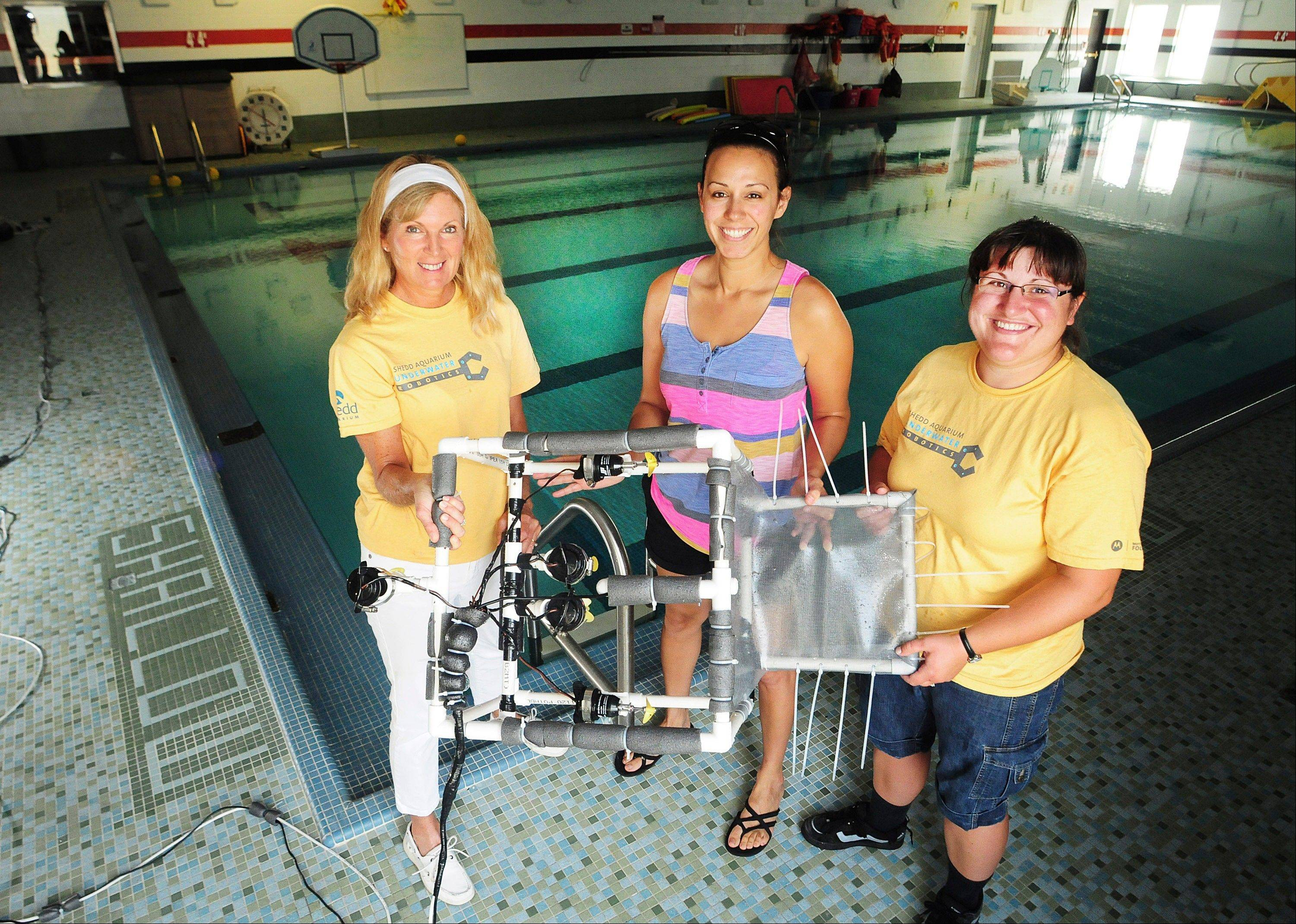 Sindy Main, left, Erica Nieto, center, and Stephanie Garner, three teachers from Carl Sandburg High School in Freeport, Ill., show off the underwater robot they built in July during a robotics workshop at Shedd Aquarium in Chicago.