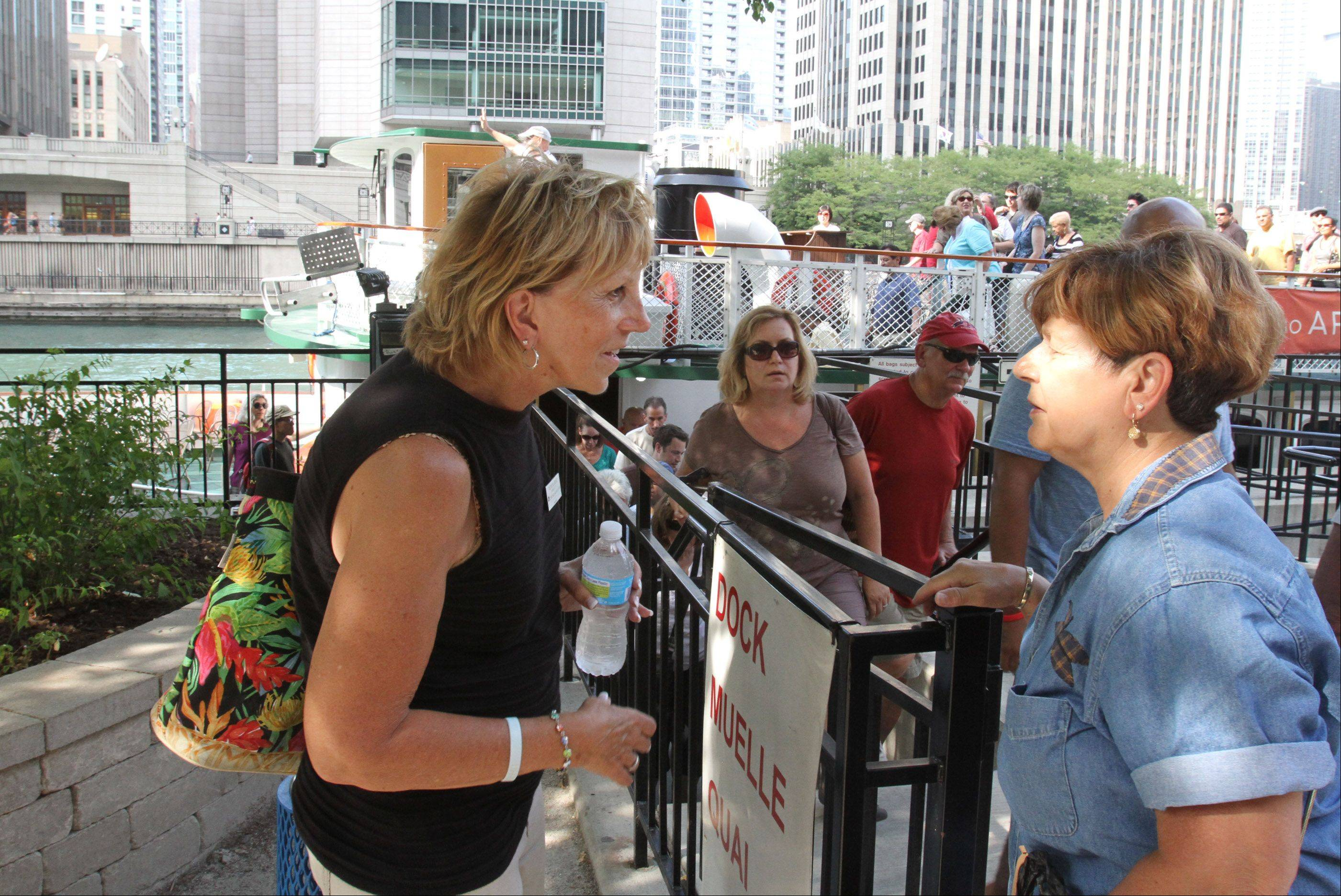 Patricia Grund, of Arlington Heights, talks with a tourist after the official Chicago Architecture Foundation river cruise. After the tour is done, Grund fields questions from passengers seeking more information about the city's buildings.
