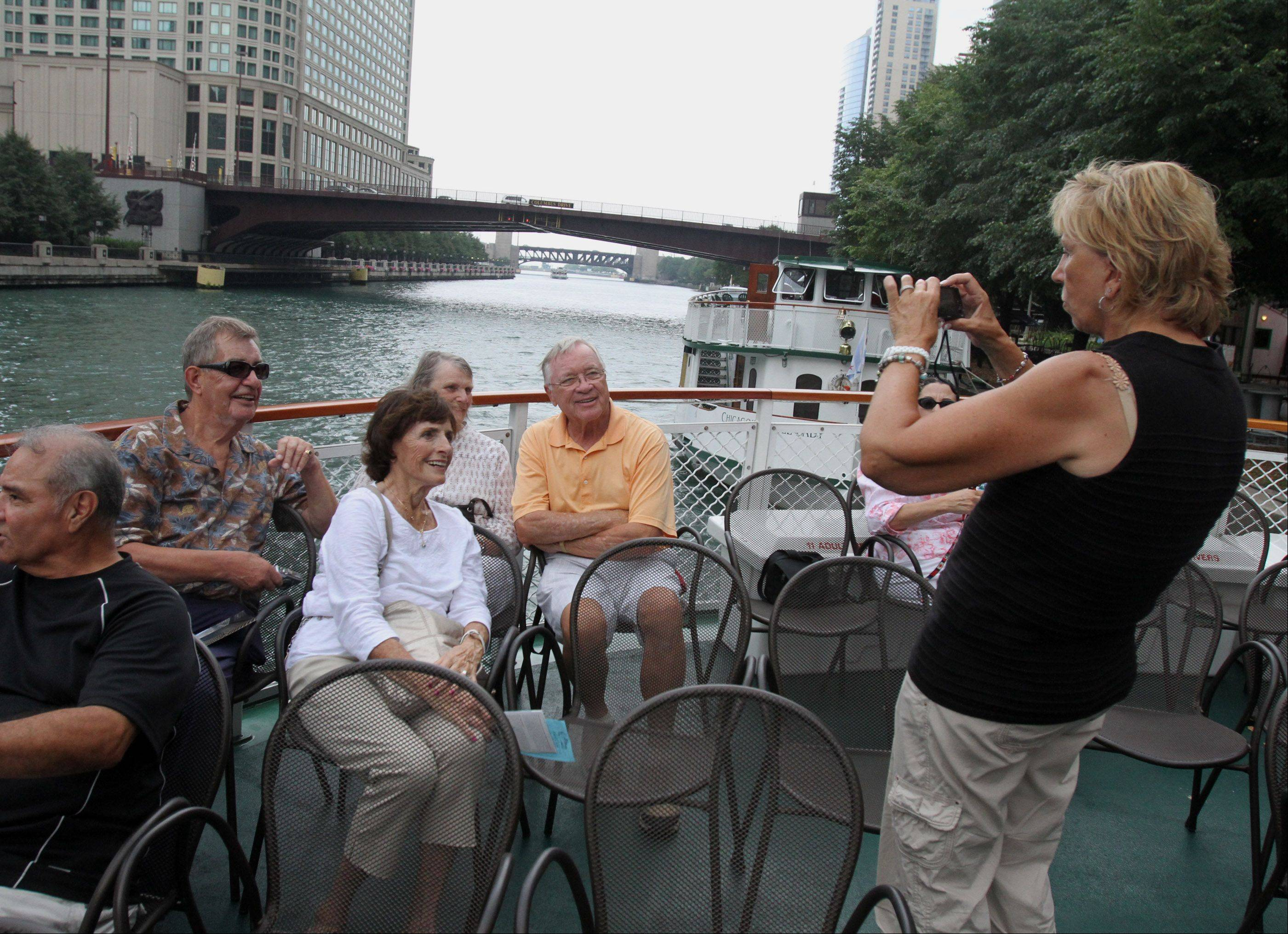 Patricia Grund of Arlington Heights, a Chicago Architecture Foundation docent, takes a picture for a tourist on board a Chicago's First Lady cruise boat.