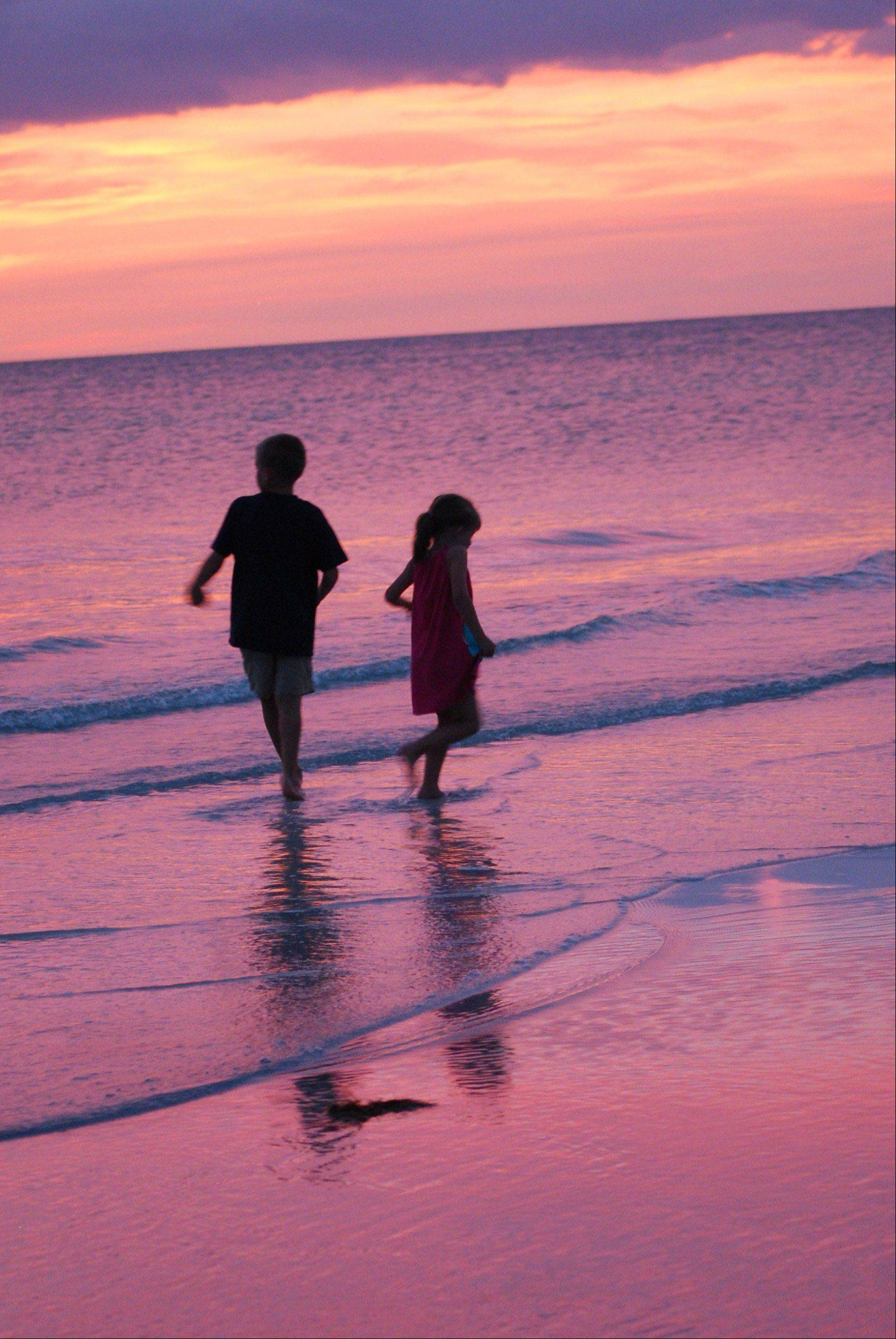 Two children walk the beach after sunset looking for sand crabs this past June at Indian Shores, Florida.