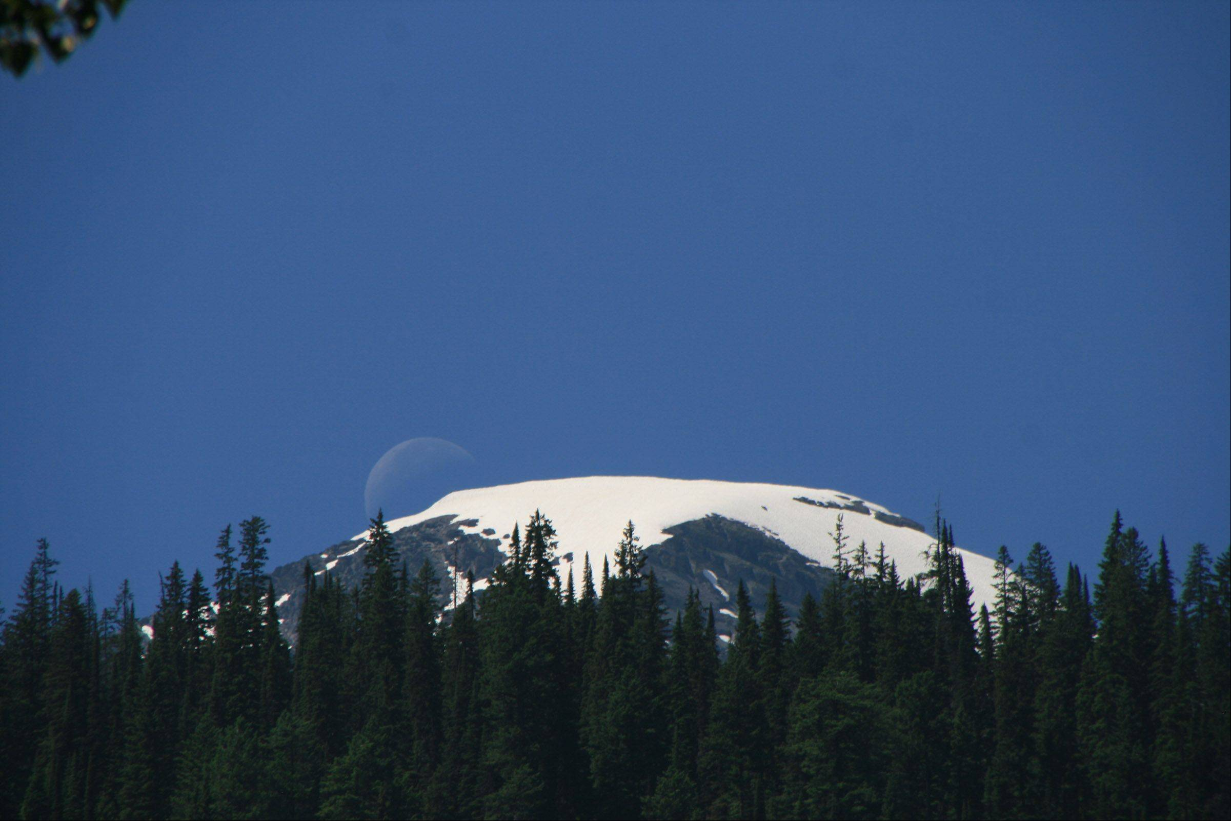 This photo was taken in Glacier National Park a few weeks ago. As I was enjoying a hike I noticed that the moon was showing clearly above this snowy peak even though it was mid afternoon. What a treasure our national parks are!