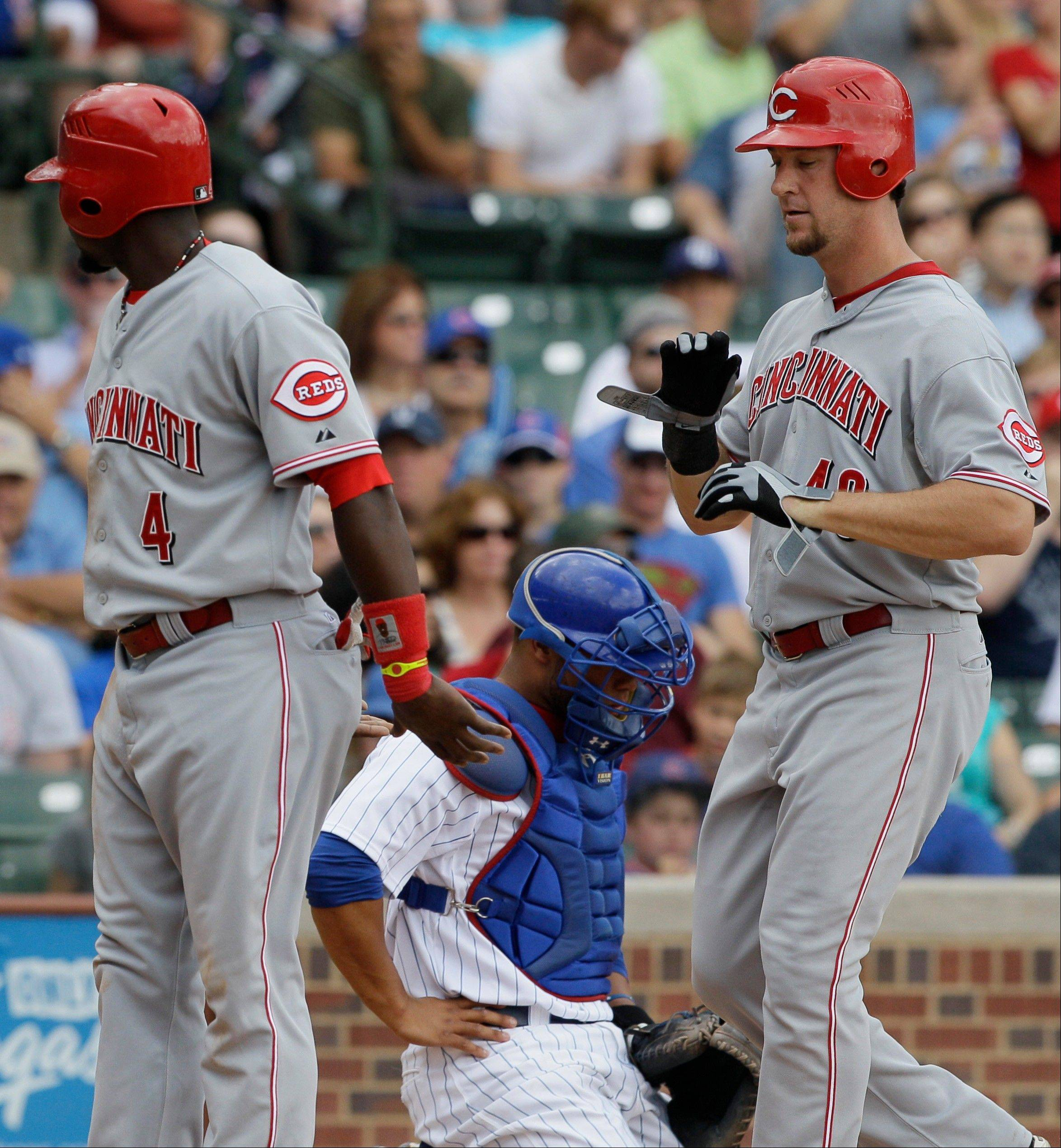 Cincinnati Reds' Ryan Ludwick, right, is congratulated by Brandon Phillips, left, after hitting a 2-run home run as Chicago Cubs catcher Welington Castillo, center, reacts as he looks down during the third inning of a baseball game in Chicago, Friday, Aug. 10, 2012.