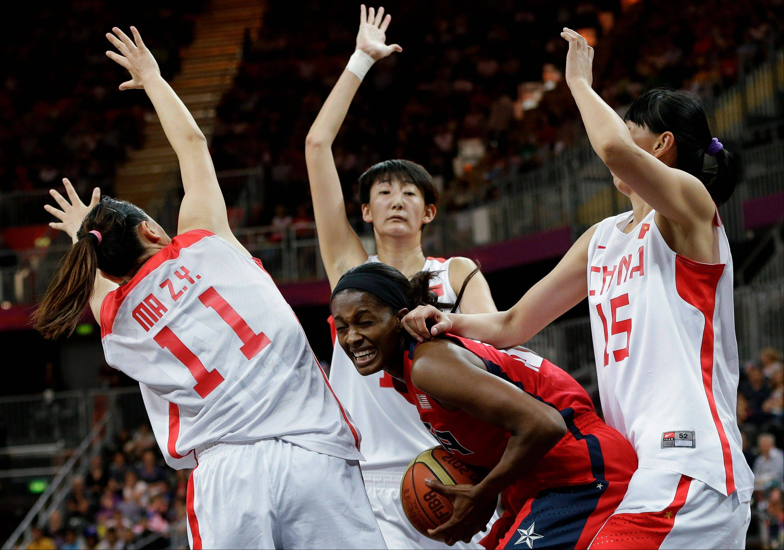 USA's Swin Cash, center, is surrounded by China defenders, Ma Zengyu (11), Wei Wei, center back, and Chen Nan (15) during a preliminary women's basketball game at the 2012 Summer Olympics, Sunday, Aug. 5, 2012, in London.