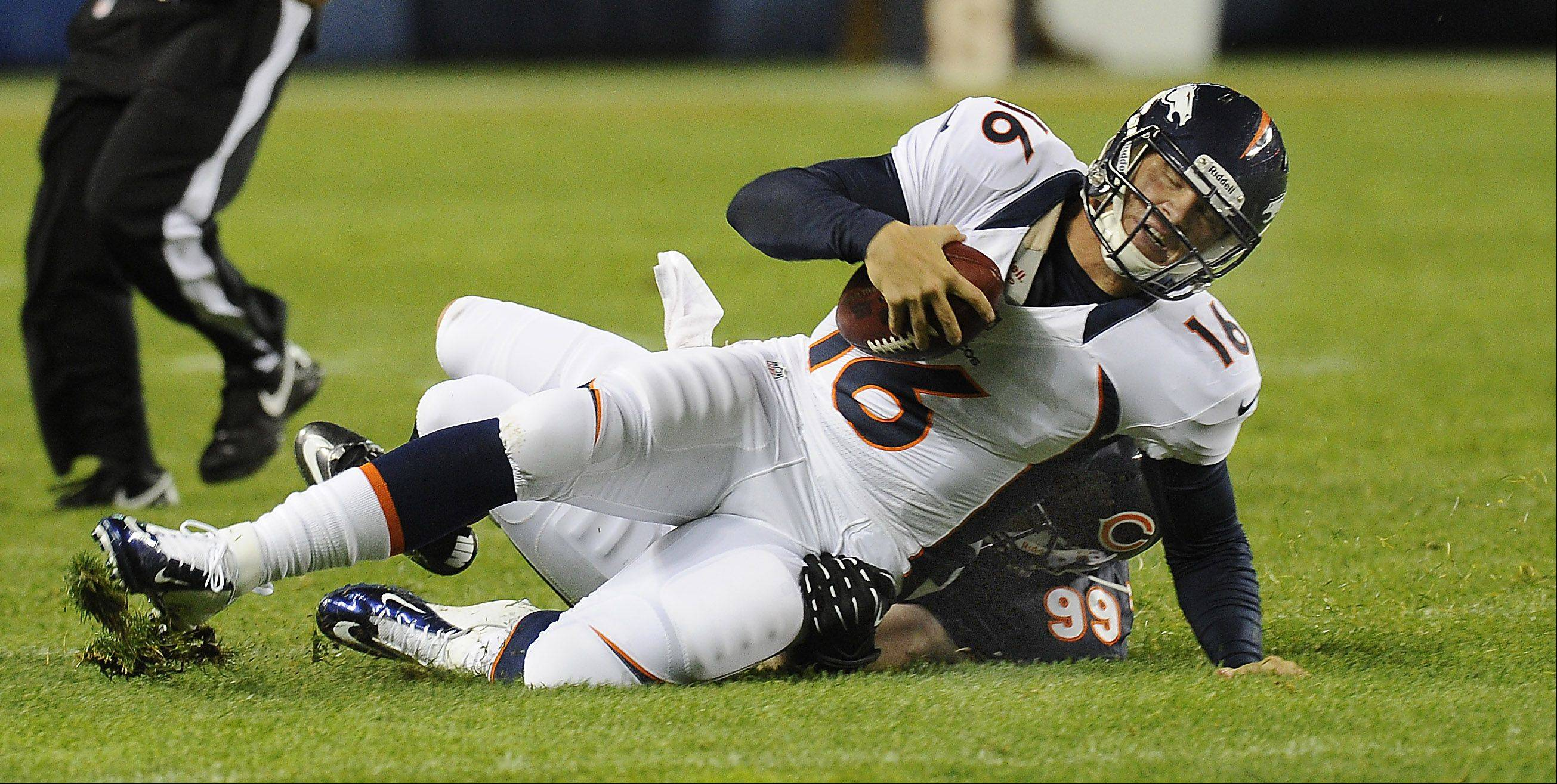 Denver Broncos quarterback Caleb Hanie is sacked by Chicago Bears Shea McClellin in the first half of game action at Soldier Field in Chicago on Thursday.