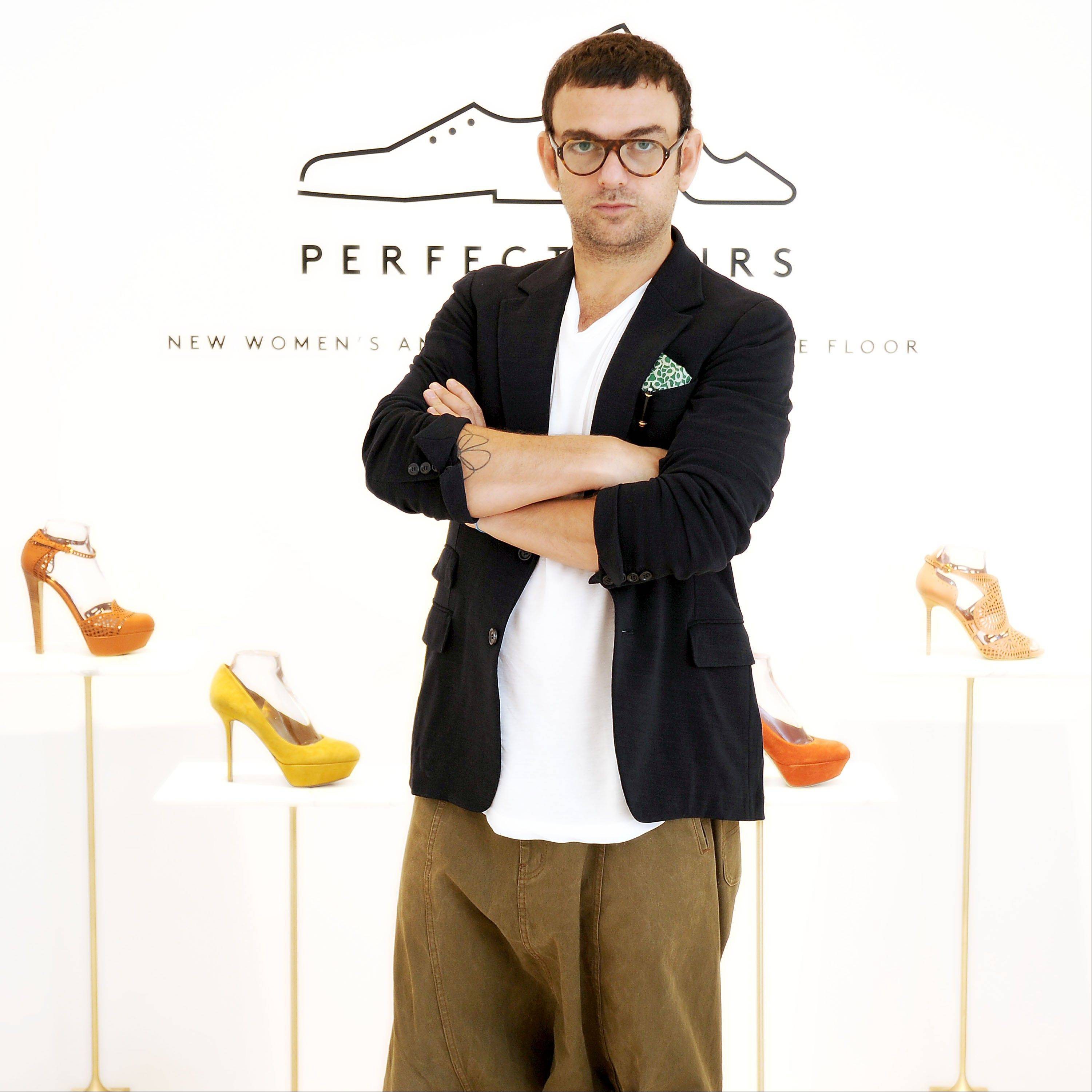 Francesco Russo, creative director for Sergio Rossi, poses in front of his fall collection at Barneys New York on July 18. Russo is flattered by the celebrities such as Anne Hathaway, Diane Kruger and Michelle Pfeiffer who wear Sergio Rossi on the red carpet, but he�s in it more for the love affair he, via shoes and handbags, will make with women of all ages and lifestyles.