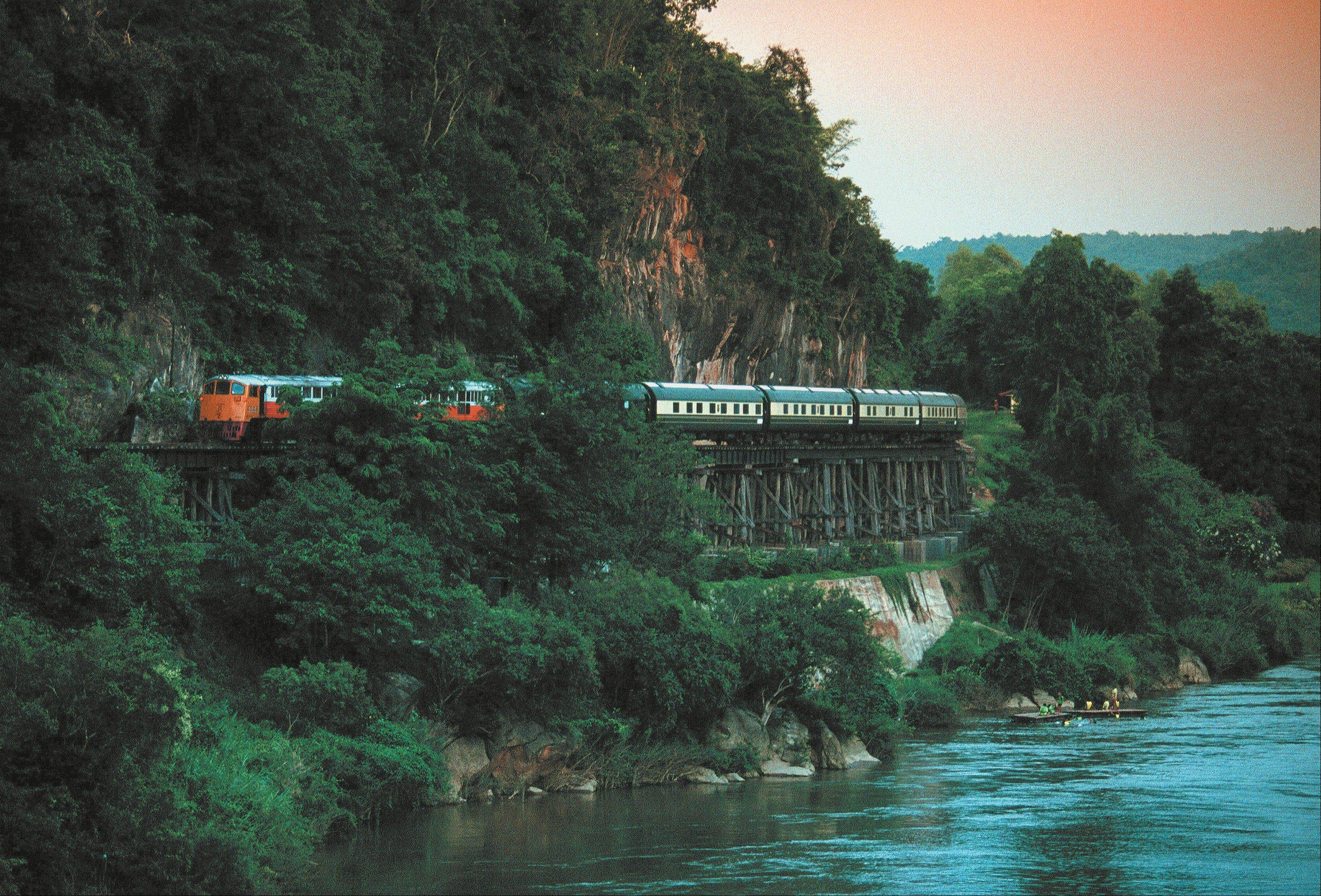 A train crosses the Kanchanaburi Bridge on the River Kwai in Thailand. The Eastern & Oriental is owned by the same company that took over the storied Orient Express, which began running between Paris and Vienna in 1883.