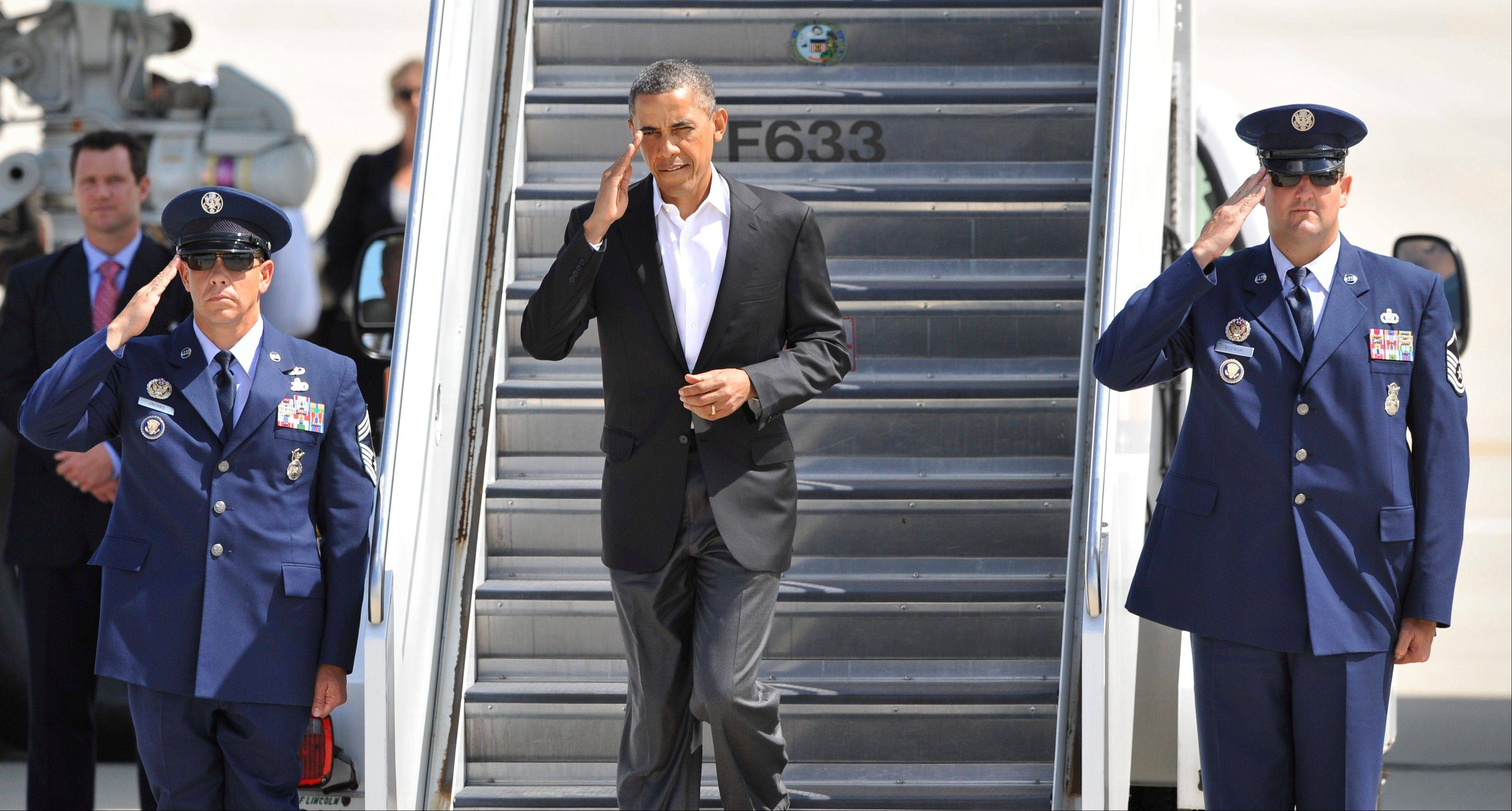 President Barack Obama salutes as he walks off Air Force One Saturday after arriving at O�Hare International Airport.