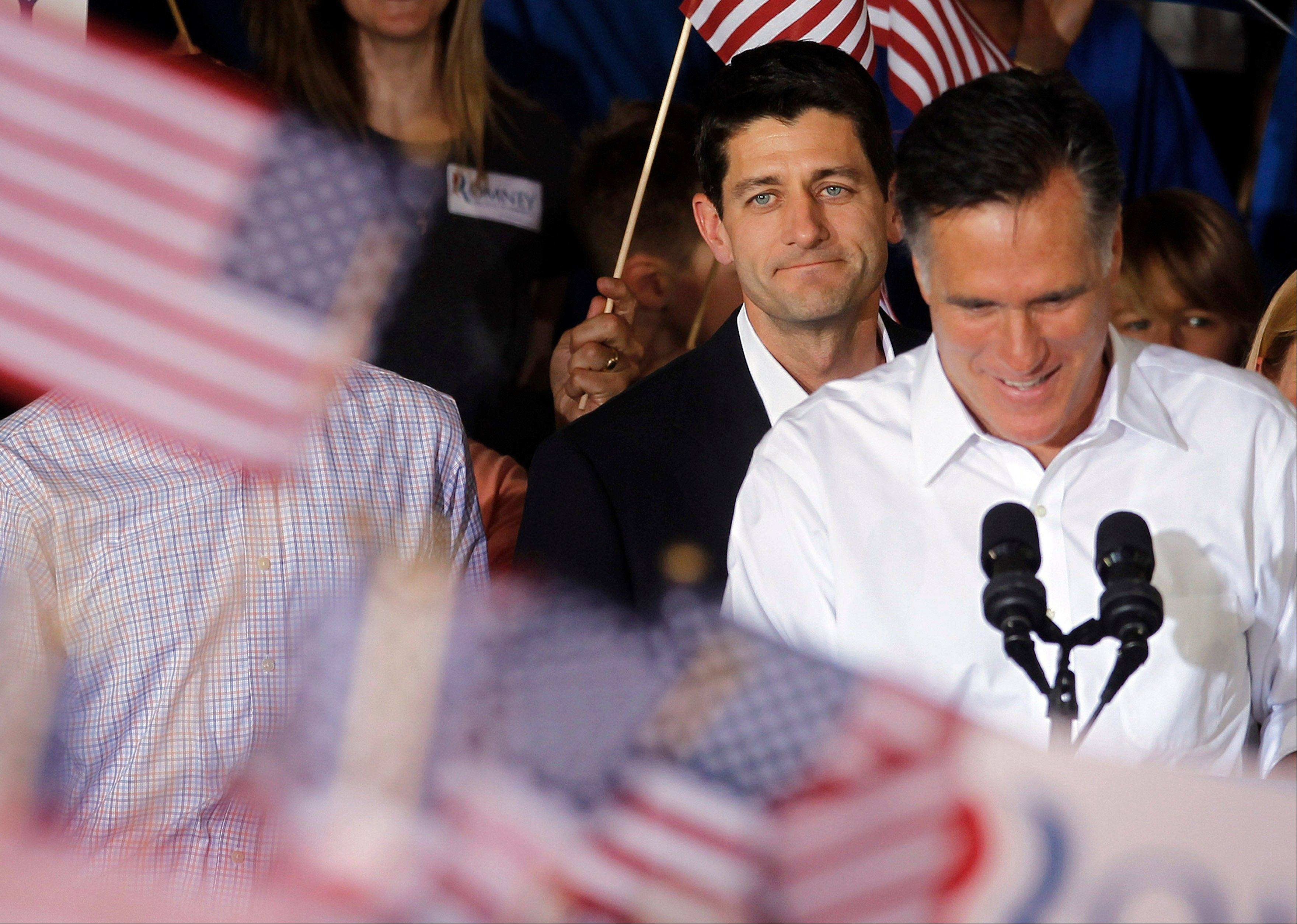 Republican presidential candidate, former Massachusetts Gov. Mitt Romney, right, with his newly announced vice presidential running mate, Wisconsin Republican Rep. Paul Ryan standing behind him, during a campaign rally Saturday in Manassas, Va.