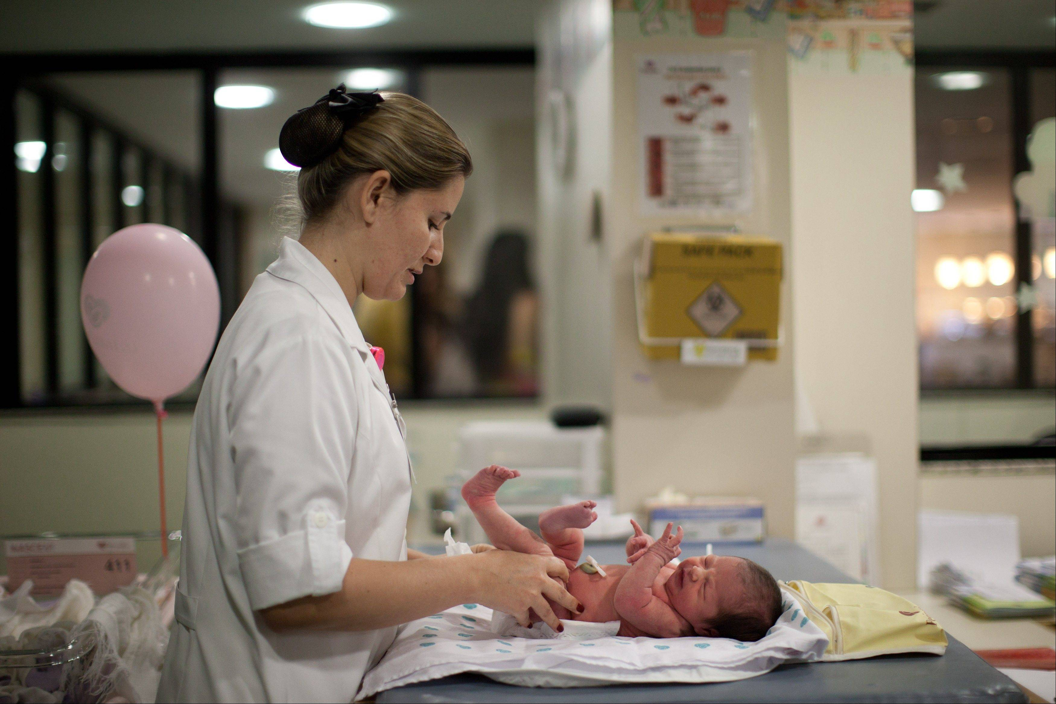 A nurse changes the diaper of a newborn baby at the Perinatal Clinic in Rio de Janeiro.