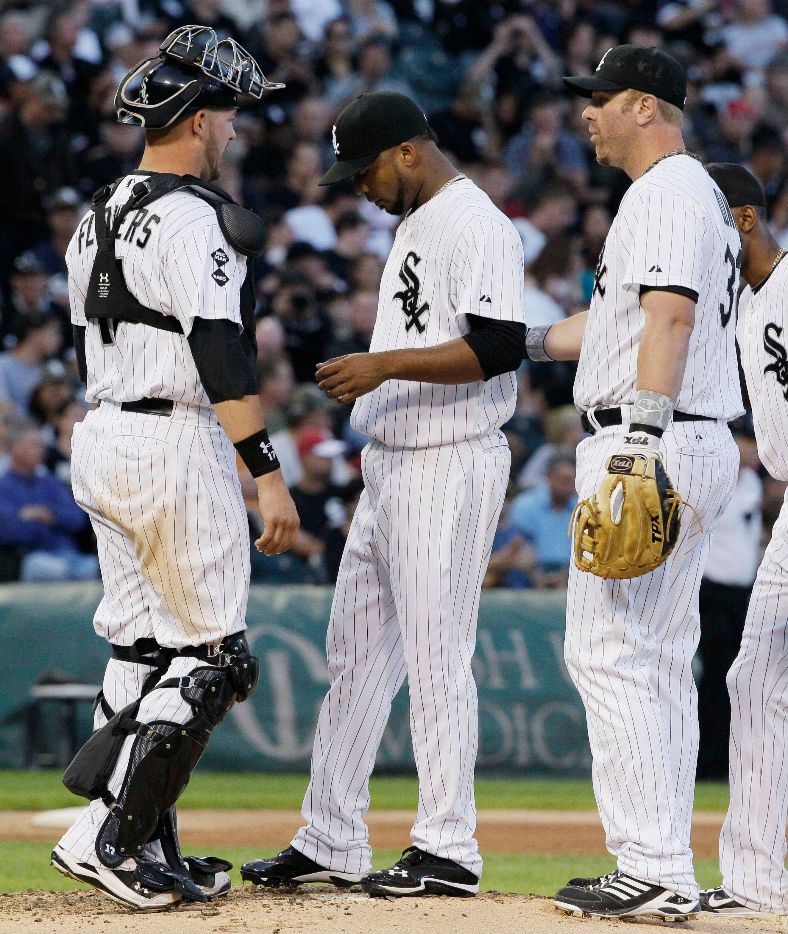 White Sox catcher Tyler Flowers and first baseman Adam Dunn talk to starter Francisco Liriano, middle, after Oakland�s Josh Reddick hit an RBI single in the fourth inning Saturday night. Liriano didn�t make it out of the fourth inning.