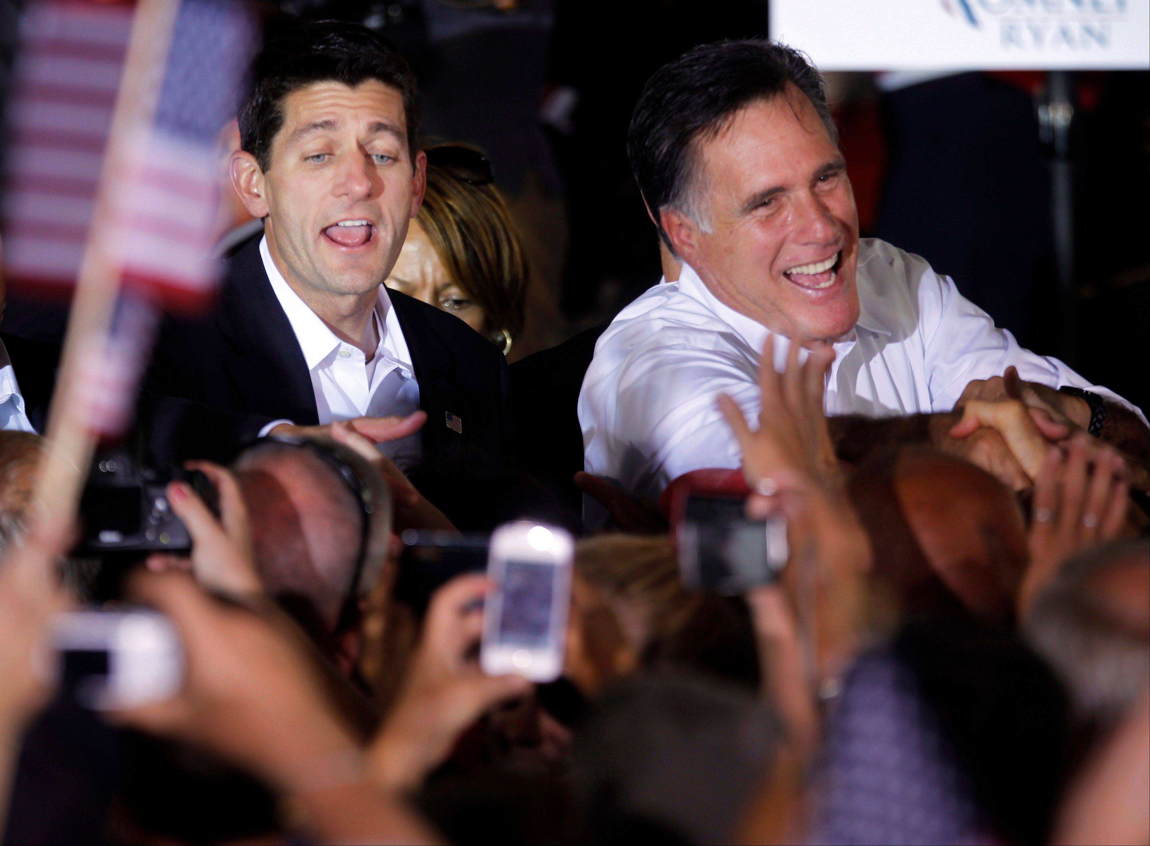 Republican presidential candidate, former Massachusetts Gov. Mitt Romney, right, and his newly announced vice presidential running mate, Rep. Paul Ryan, R-Wis., left, greet supporters Saturday during a campaign rally in Manassas, Va.