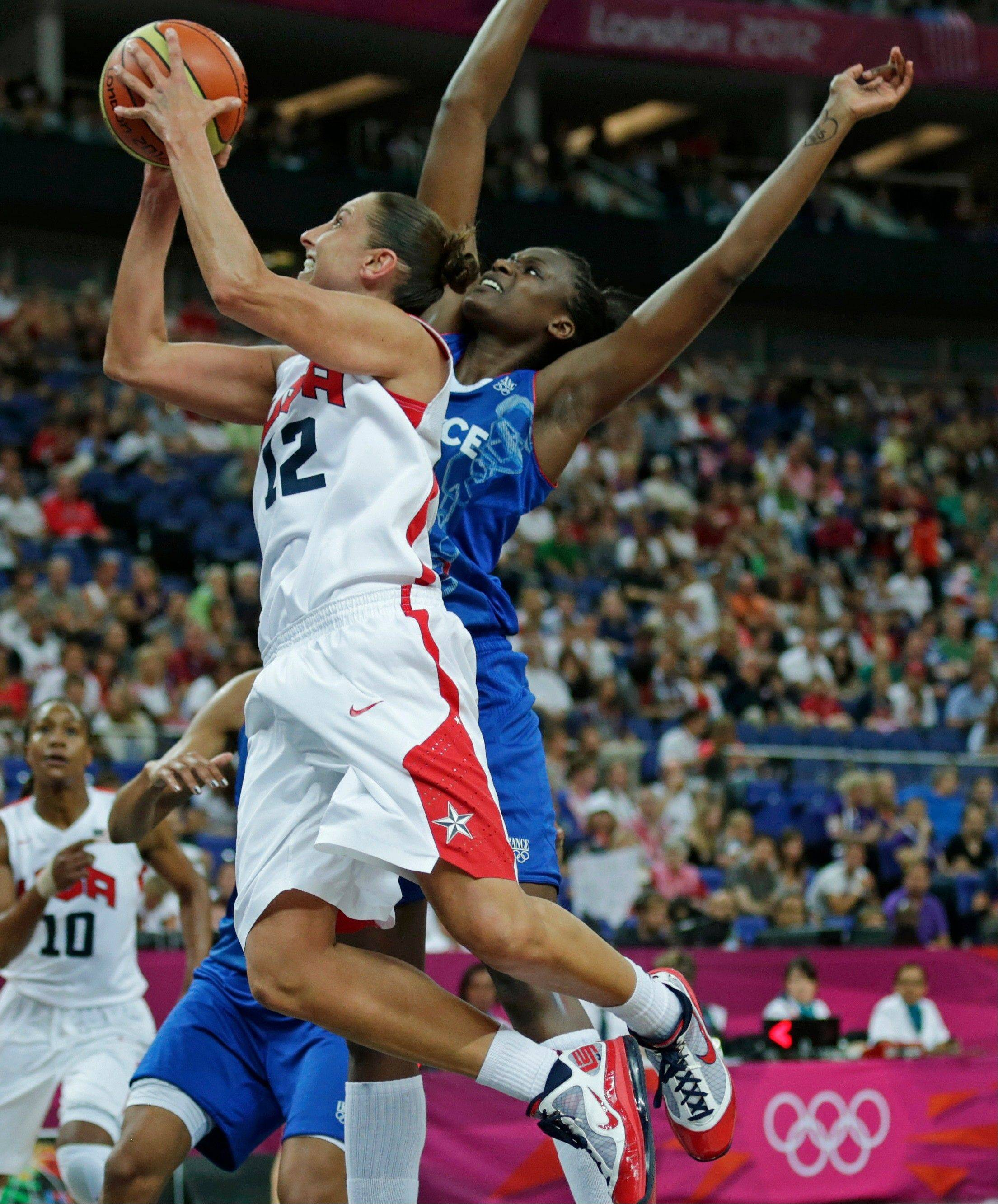 United States' Diana Taurasi (12) drives to the basket against France's Jennifer Digbeu during the women's gold medal basketball game at the 2012 Summer Olympics, Saturday, Aug. 11, 2012, in London.