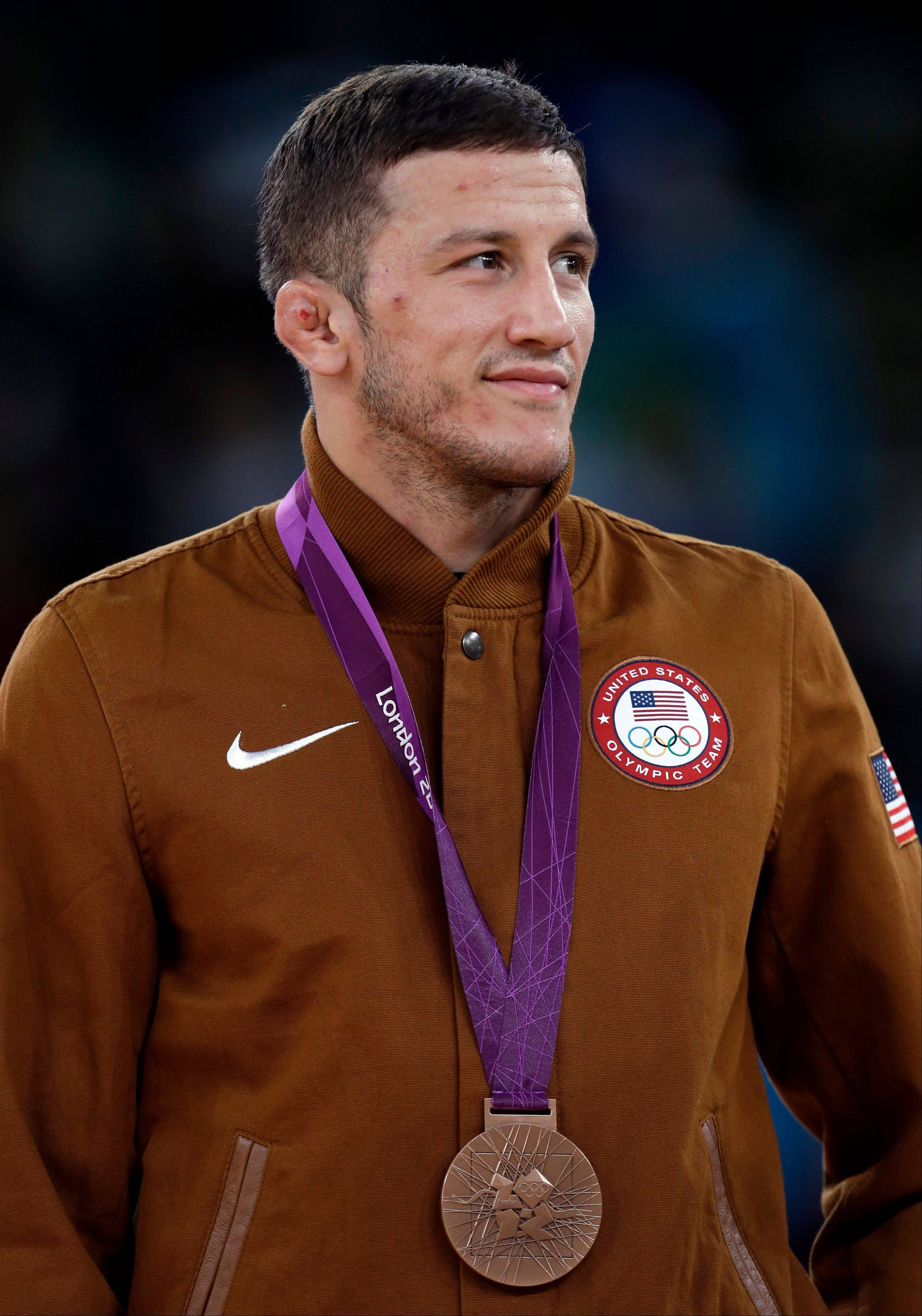 Bronze medalist Coleman Scott of the United States poses with his medal during the victory ceremony for the men's 60-kg freestyle wrestling competition at the 2012 Summer Olympics, Saturday, Aug. 11, 2012, in London.