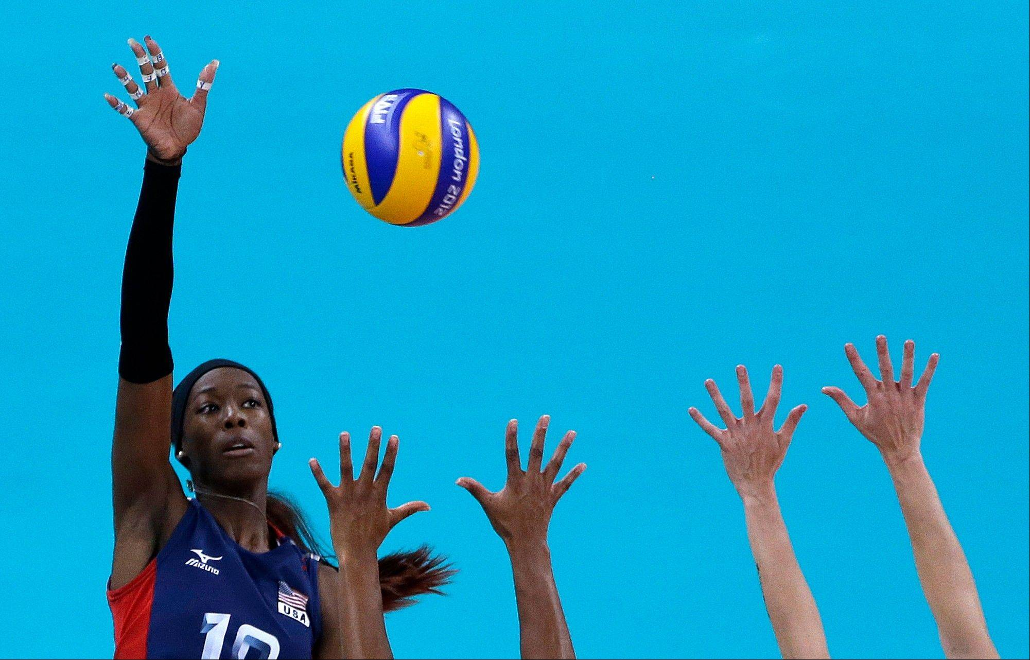 United States' Destinee Hooker, left, spikes the ball over defenders from Brazil during a women's gold medal volleyball match at the 2012 Summer Olympics, Saturday, Aug. 11, 2012, in London.