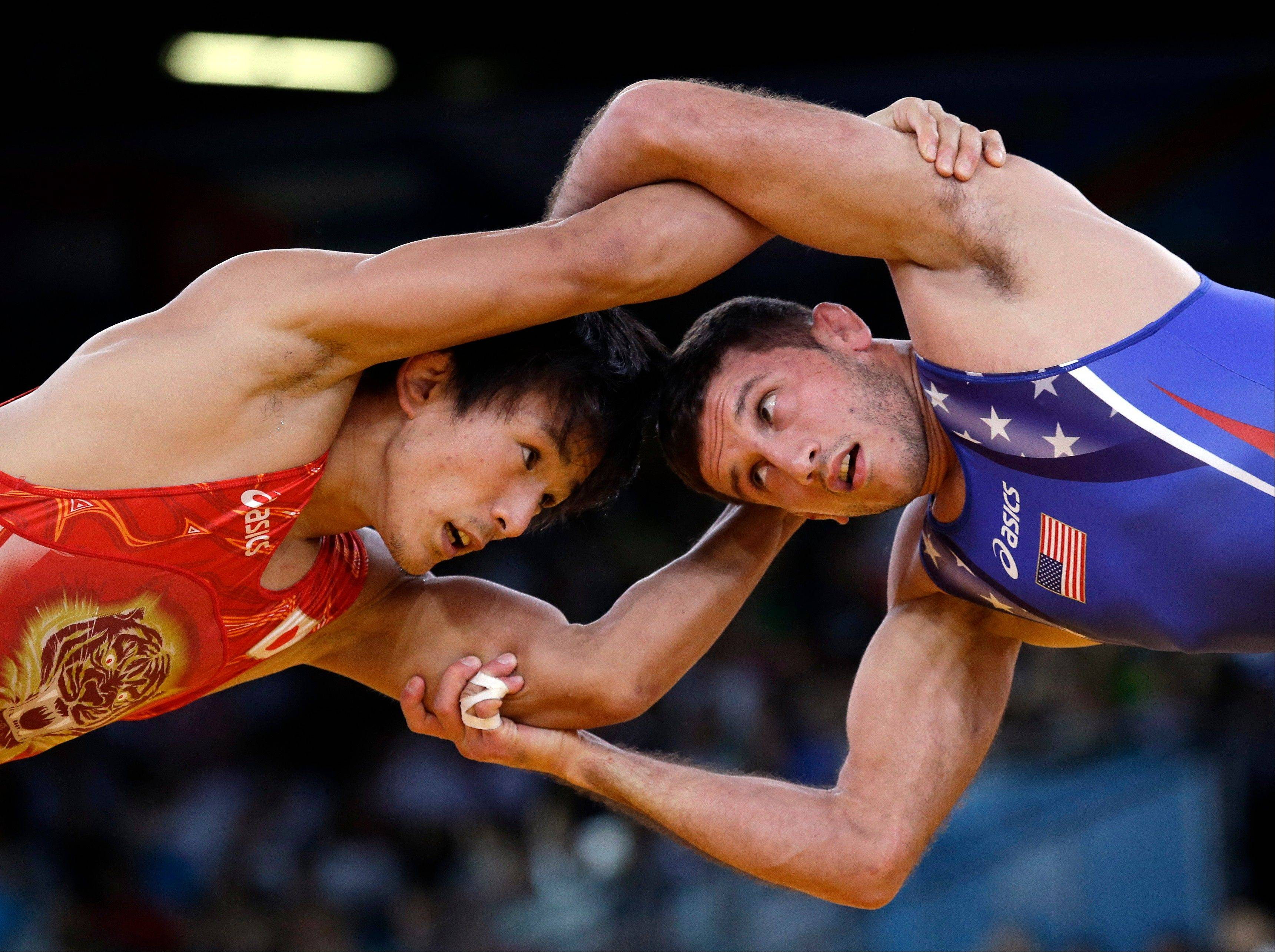 Coleman Scott of the United States competes against Kenichi Yumoto of Japan (in red) for the bronze medal during the men's 60-kg freestyle wrestling competition at the 2012 Summer Olympics, Saturday, Aug. 11, 2012, in London.